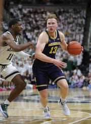 Michigan forward Ignas Brazdeikis drives against Michigan State forward Aaron Henry during first half action Saturday, March 9, 2019 at the Breslin Center in East Lansing, Mich.