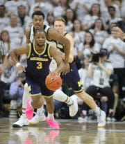 Michigan guard Zavier Simpson steals the ball from Michigan State forward Xavier Tillman during first half action Saturday, March 9, 2019 at the Breslin Center in East Lansing, Mich.
