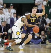 Michigan forward Ignas Brazdeikis defendsMichigan State guard Cassius Winston during first half action Saturday, March 9, 2019 at the Breslin Center in East Lansing, Mich.