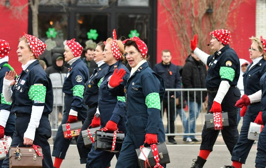 Women dressed as Rosie the Riveter walk in the 61st annual St. Patrick's Day Parade on Michigan Avenue in Detroit on Mar. 10, 2019.