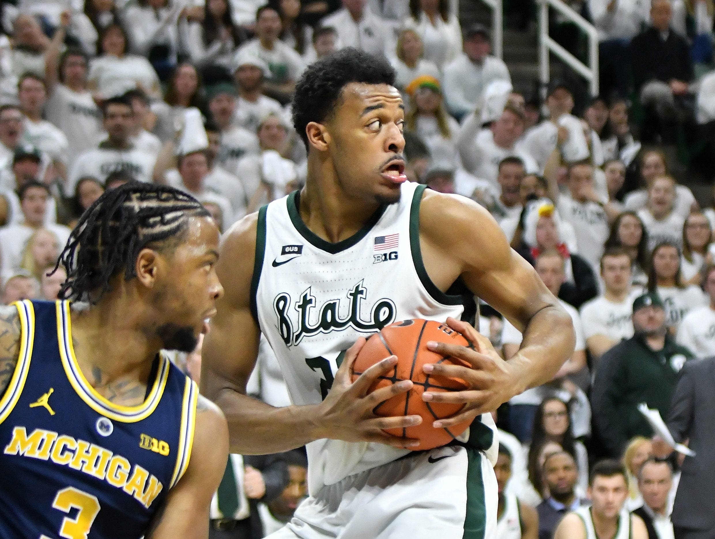 Michigan State forward Xavier Tillman (23) comes up with the ball after blocking  a shot by Michigan guard Zavier Simpson (3) in the first half.   Michigan vs Michigan State at the Breslin Center in East Lansing, Mich. on Mar. 9, 2019.  (Robin Buckson / Detroit News)