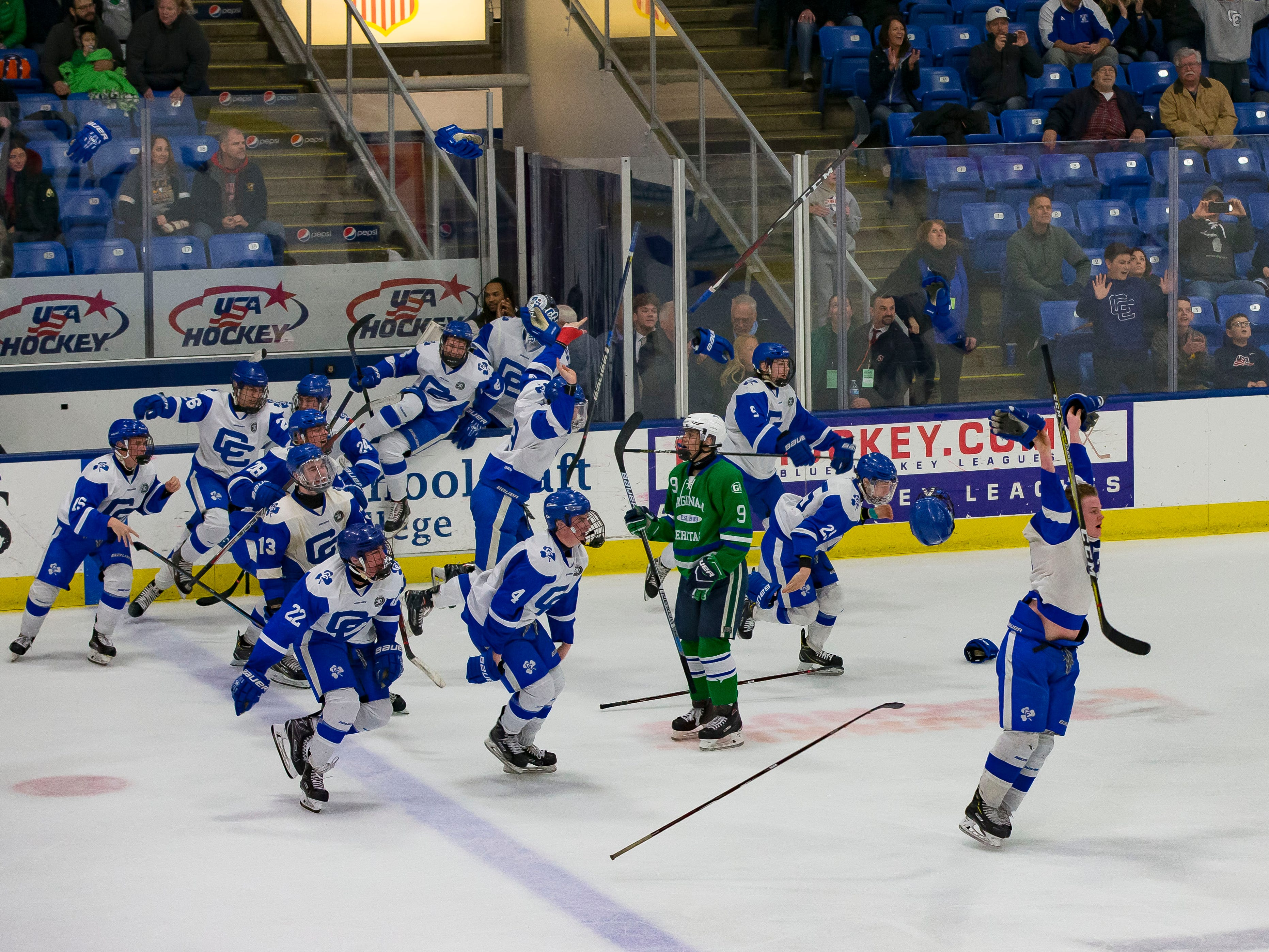 Players from Catholic Central celebrate at the buzzer after defeating the Saginaw Heritage to win the MHSAA Division 1 championship game, 3-1, at USA Arena  in Plymouth.