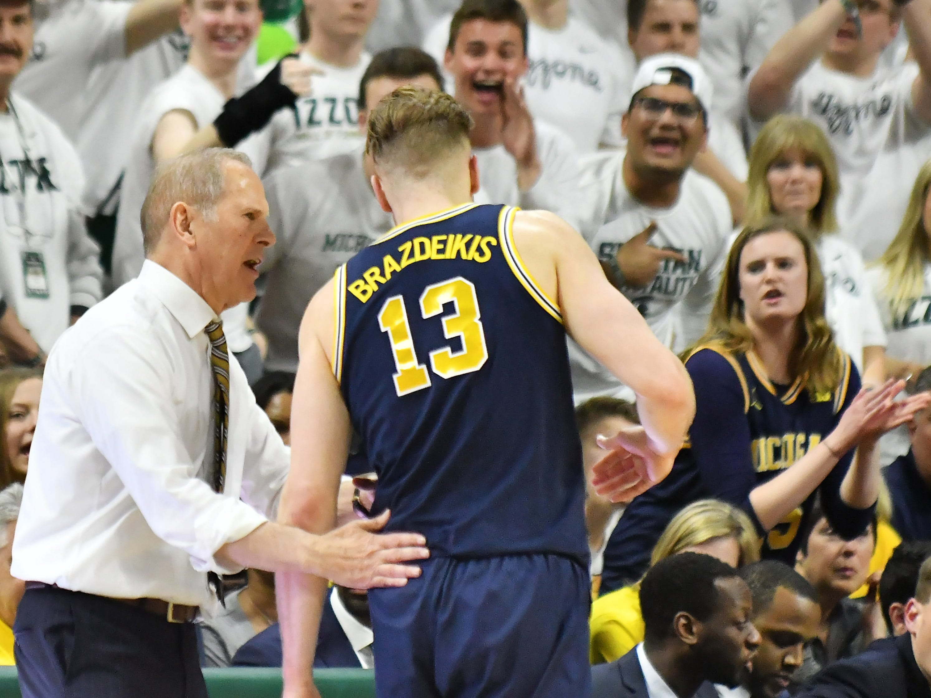 Michigan head coach John Beiliein talks with Michigan forward Ignas Brazdeikis (13) when he comes out of the game in the second half.