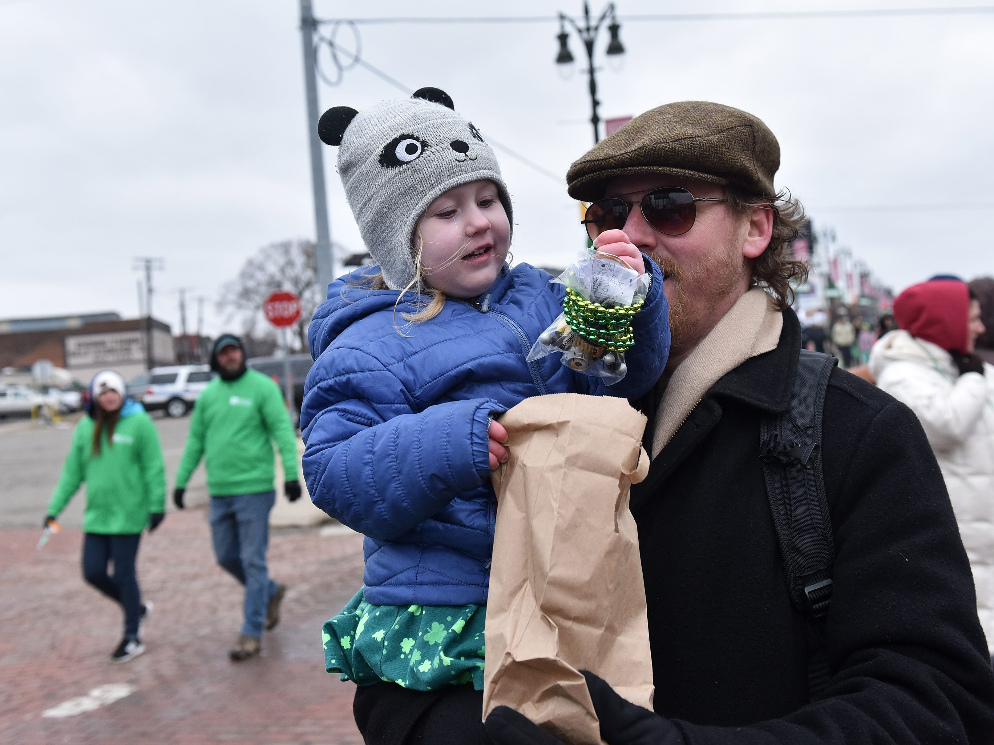 Thea Maher, 3, pulls beads and toys out of the bag with her dad, Eric Maher of West Bloomfield. The goodies were handed out by Michael and Maureen Hogan from the Gaelic League at the parade.