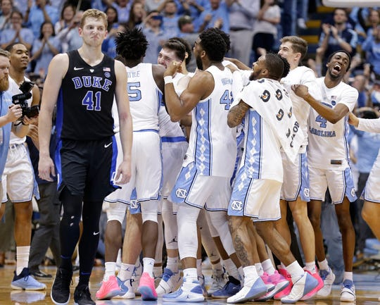 North Carolina players celebrate while Duke's Jack White (41) walks away after the Tar Heel's 79-70 victory Saturday.