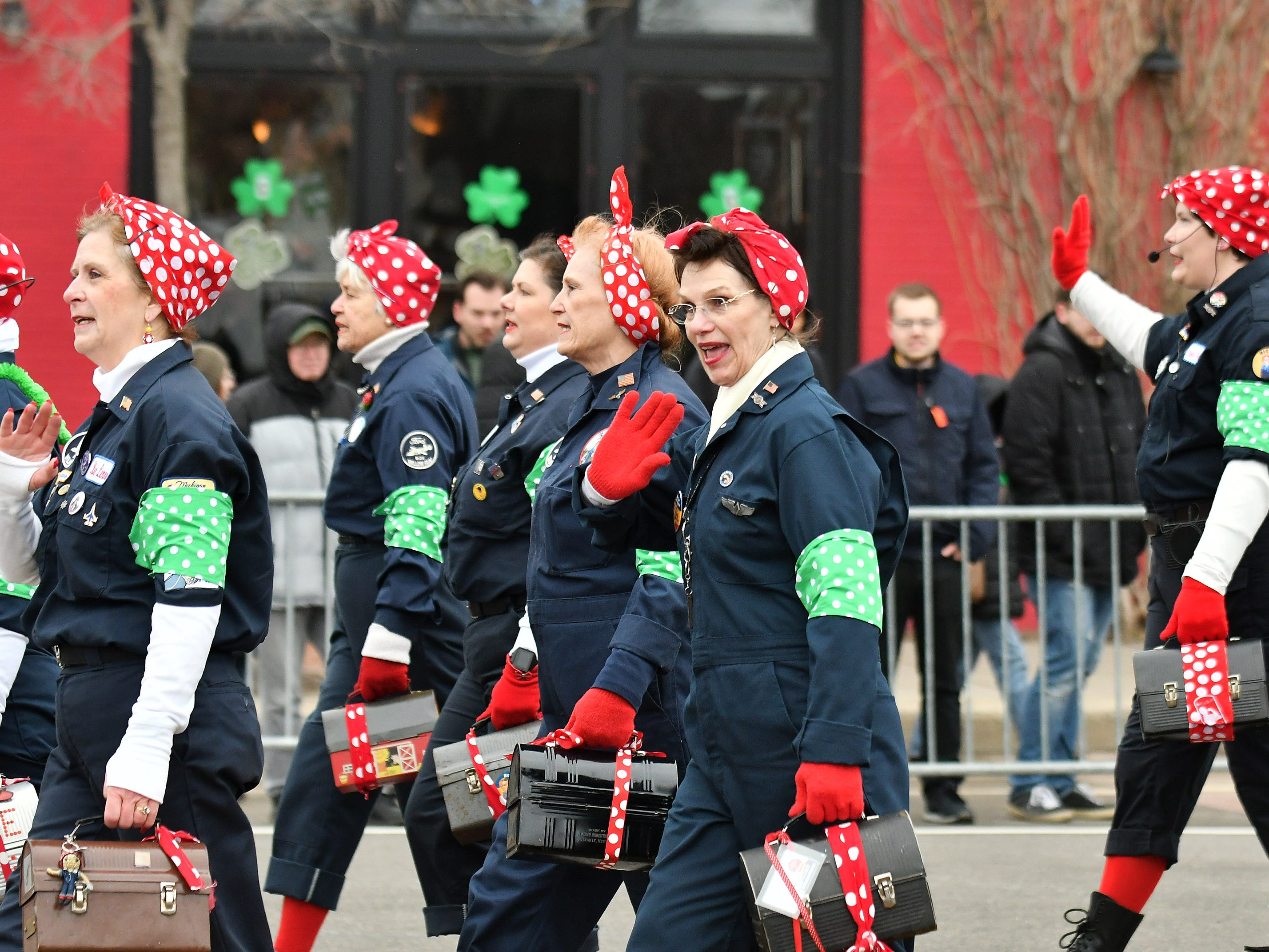 Women dressed as Rosie the Riveter walk in the 61st annual St. Patrick's Day Parade.