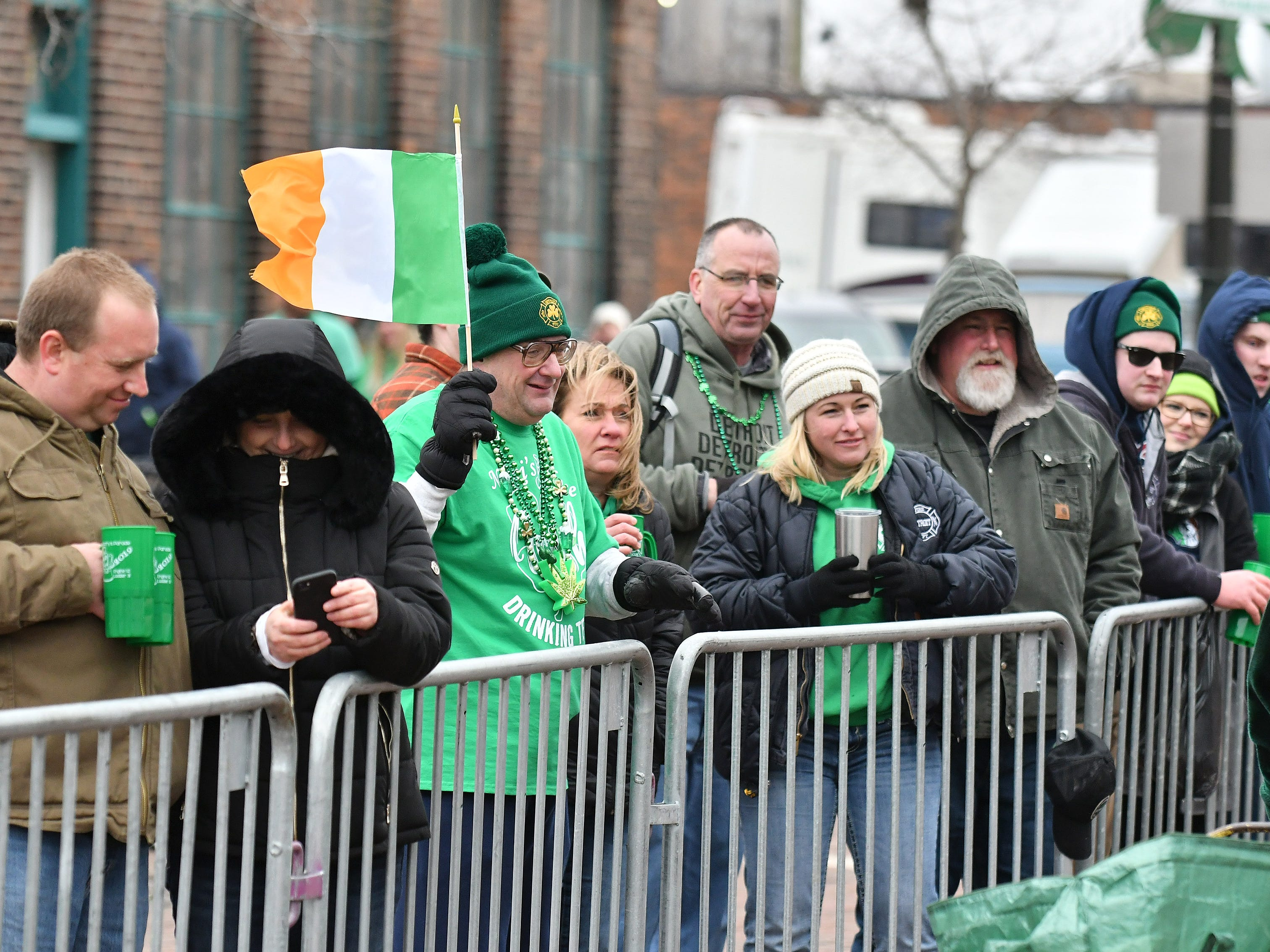 Dave Long, 52, of Detroit, center, holds an Irish flag at the parade.