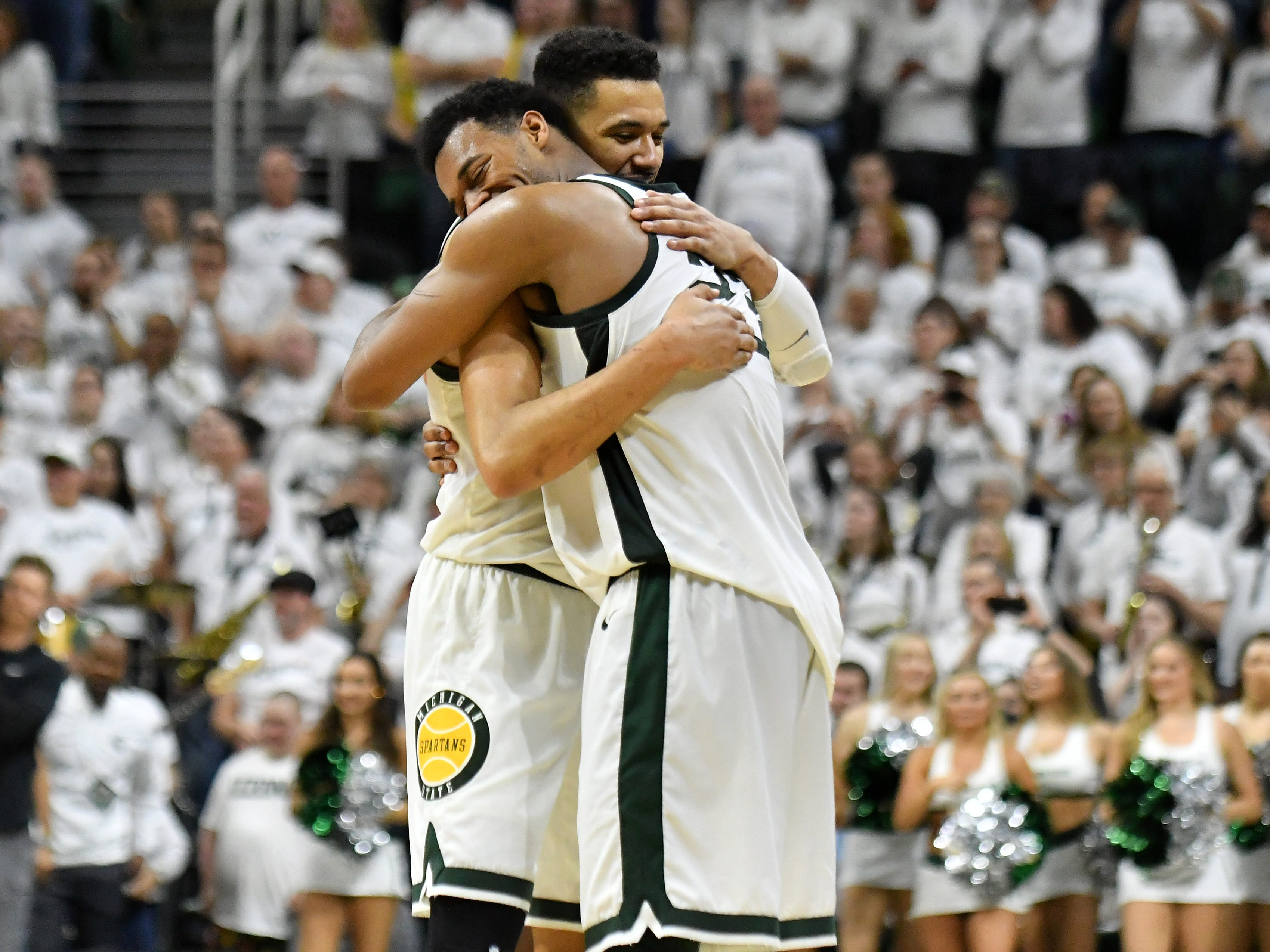 Michigan State forward Xavier Tillman (23) hugs Michigan State senior forward Kenny Goins, left, before Goins exits the game late in the second half.