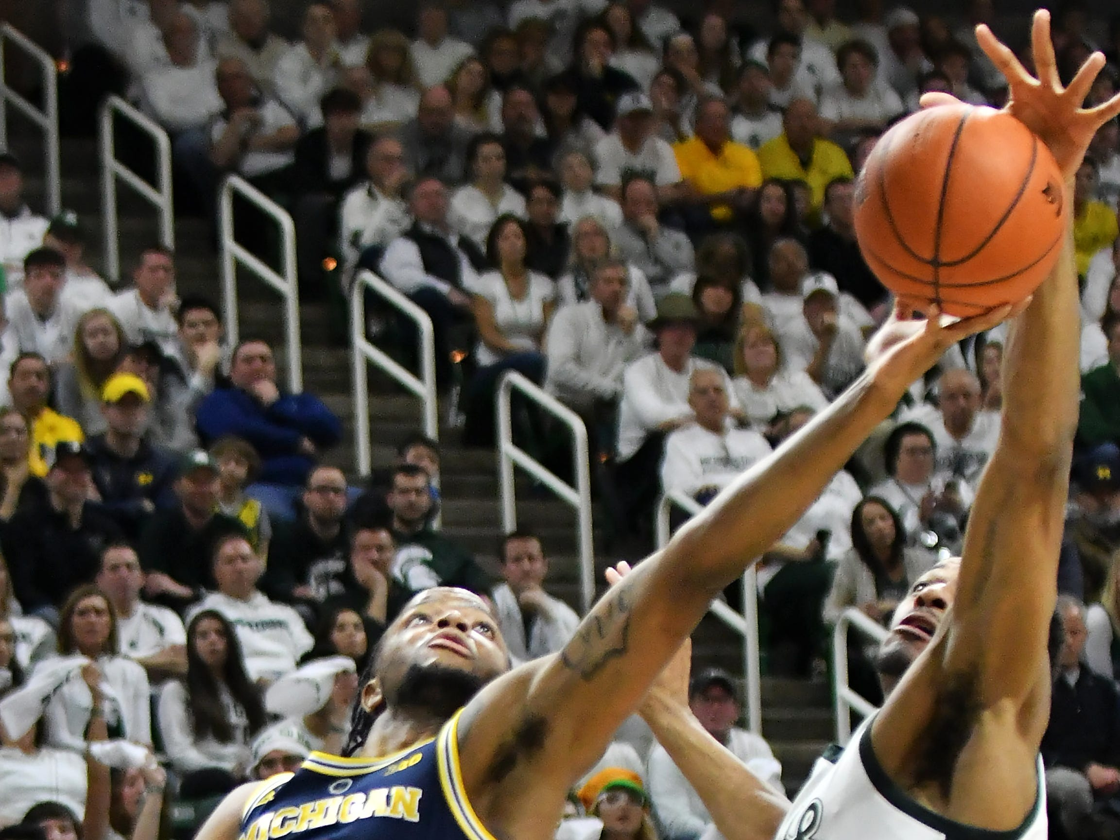 Michigan State forward Xavier Tillman (23) blocks a shot by Michigan guard Zavier Simpson (3) in the first half.