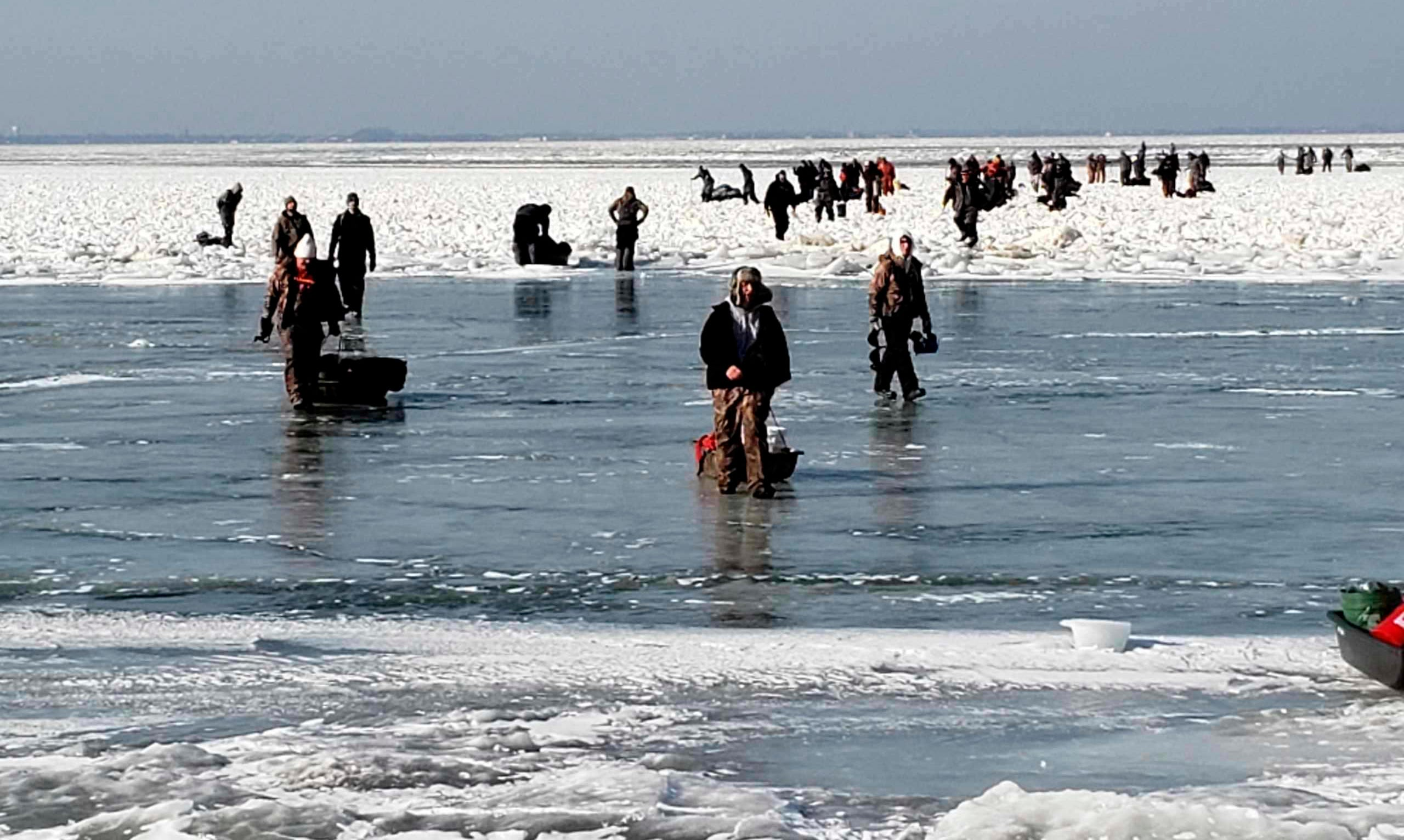 Ice fishermen walk to land after being stuck on an ice floe that broke free from land north of Catawba Island, Saturday, March 9, 2019, in Ohio.