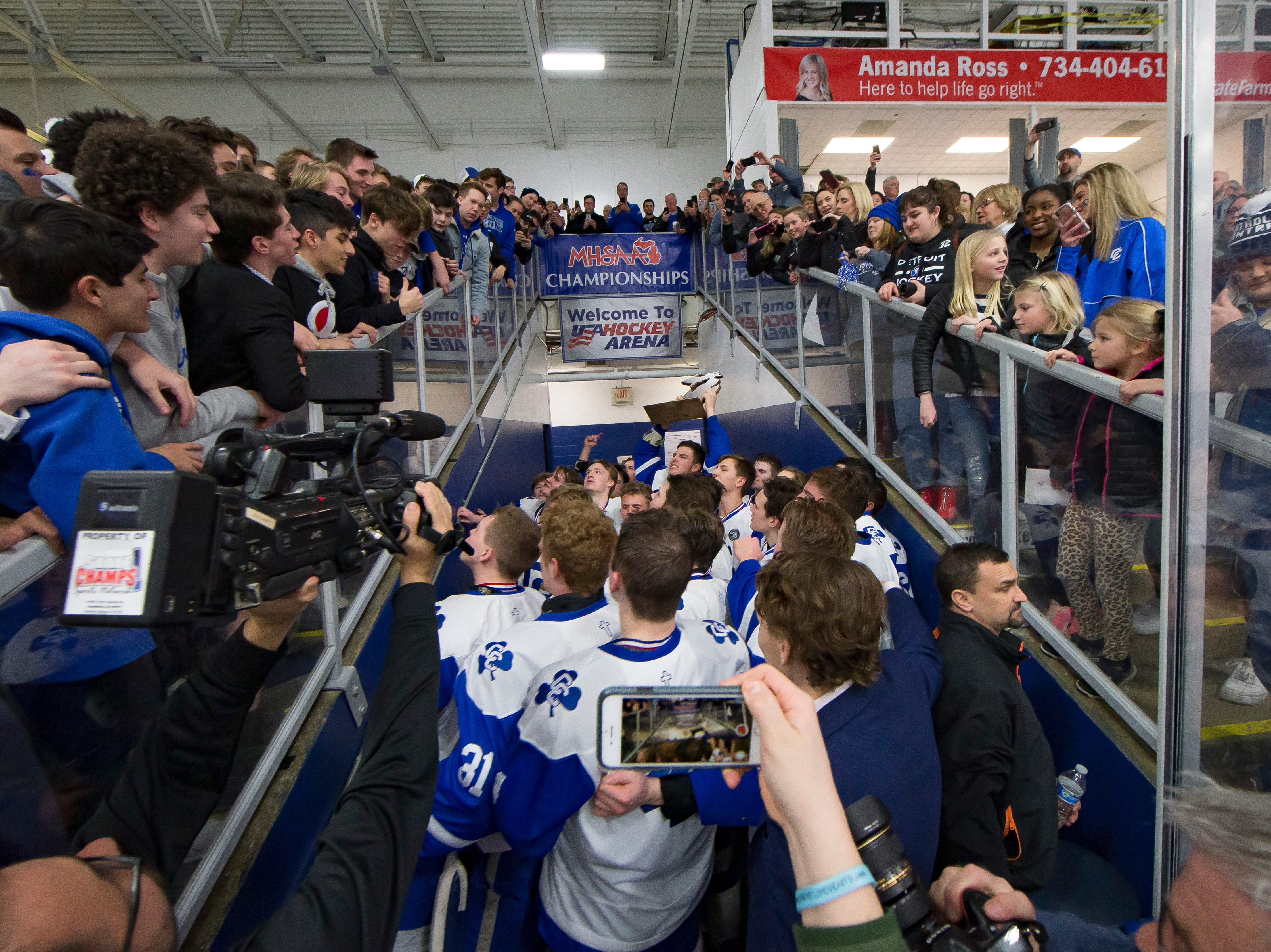 Catholic Central players celebrate with the fans on their way to the locker room after defeating Saginaw Heritage 3-1.