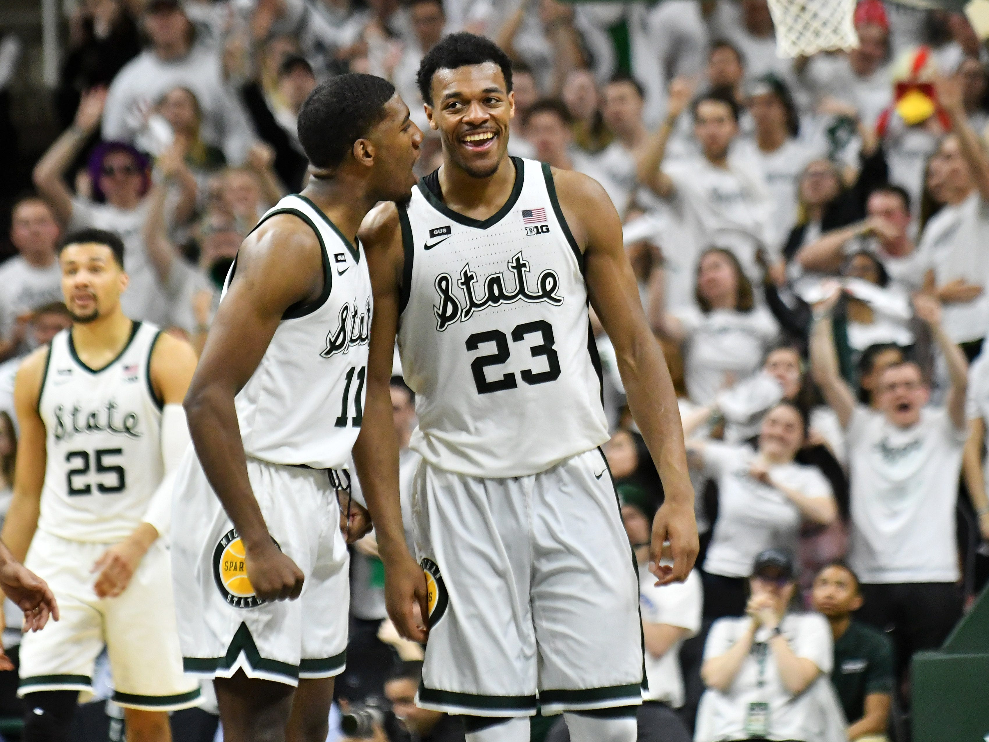 Michigan State forward Aaron Henry (11) shares a moment with Michigan State forward Xavier Tillman (23) while Michigan State leads in the second half.