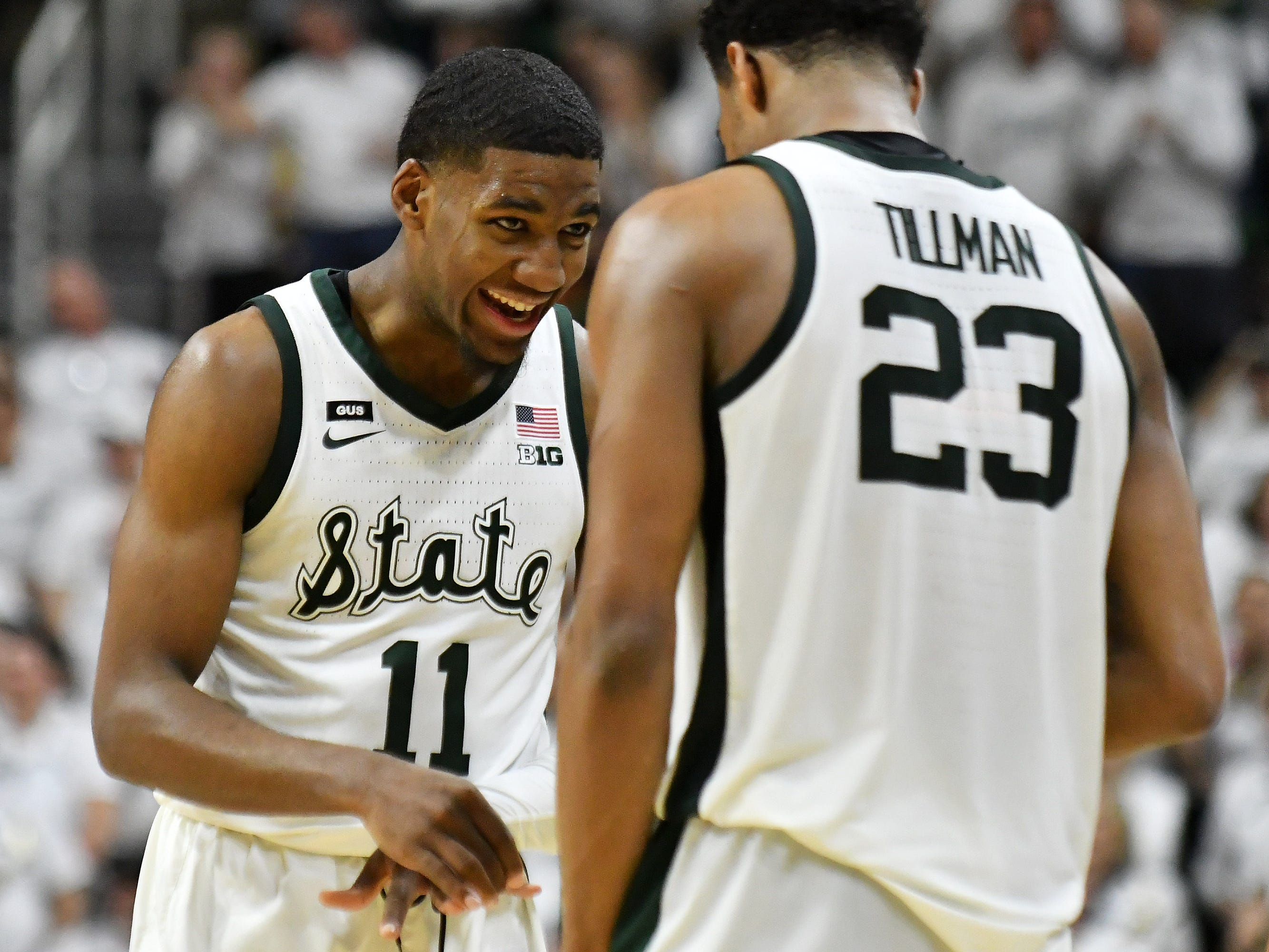 Michigan State forward Aaron Henry (11) shares a moment with Michigan State forward Xavier Tillman (23) in the second half.