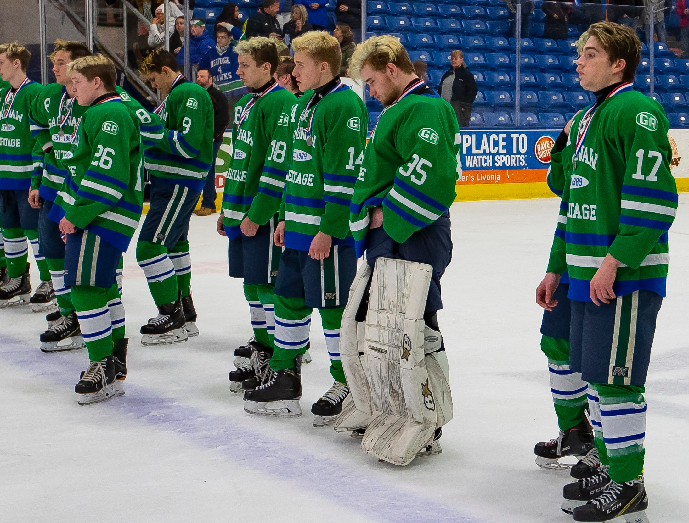 Players from Saginaw Heritage stand dejected during postgame ceremonies after losing to Detroit Catholic Central 3-1 during the MHSAA Division 1 Finals.