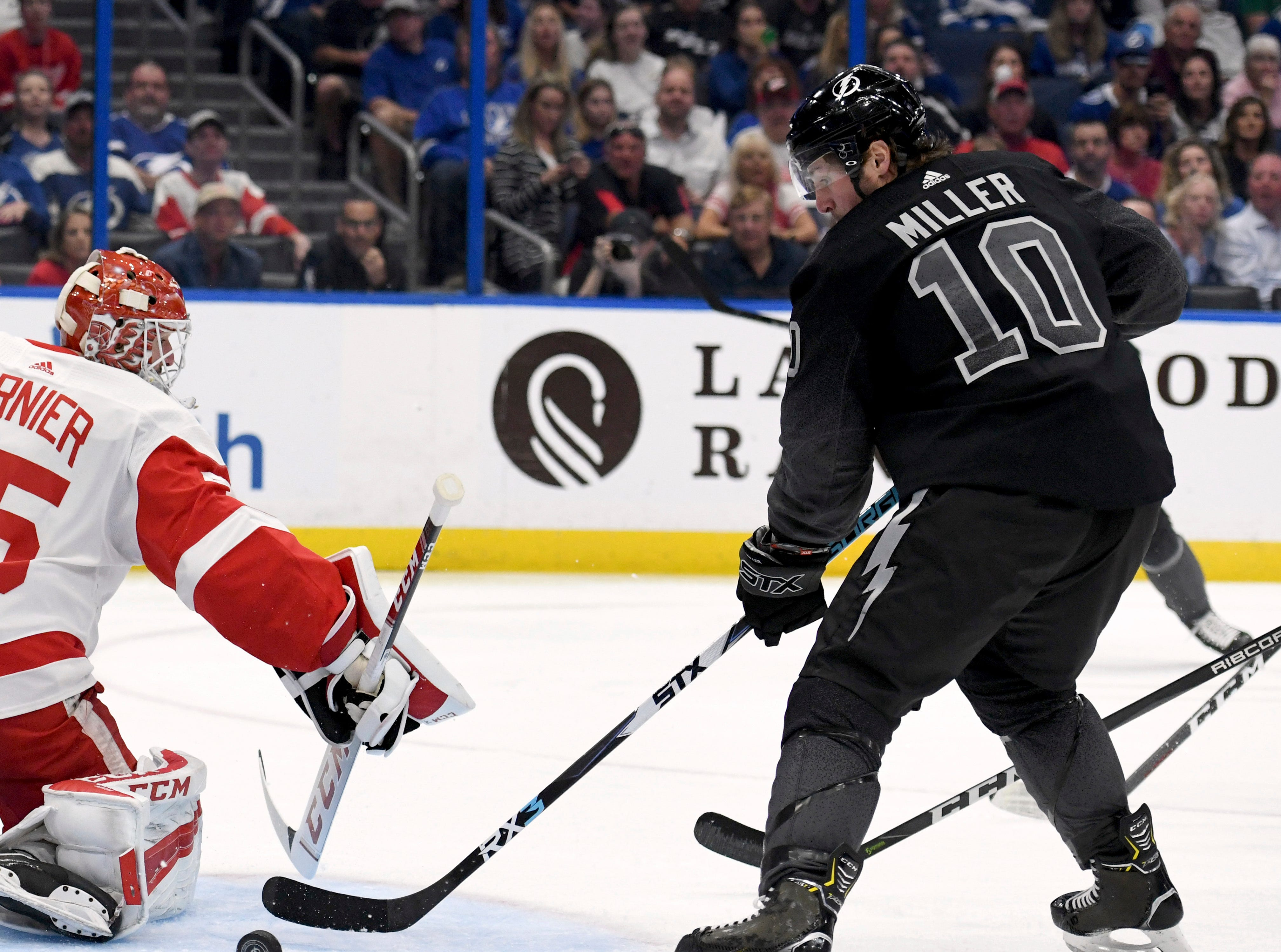 Detroit Red Wings goaltender Jonathan Bernier (45) deflects a shot wide of the net as Tampa Bay Lightning center J.T. Miller (10) looks for a shot during the second period of an NHL hockey game Saturday, March 9, 2019, in Tampa, Fla. (AP Photo/Jason Behnken)