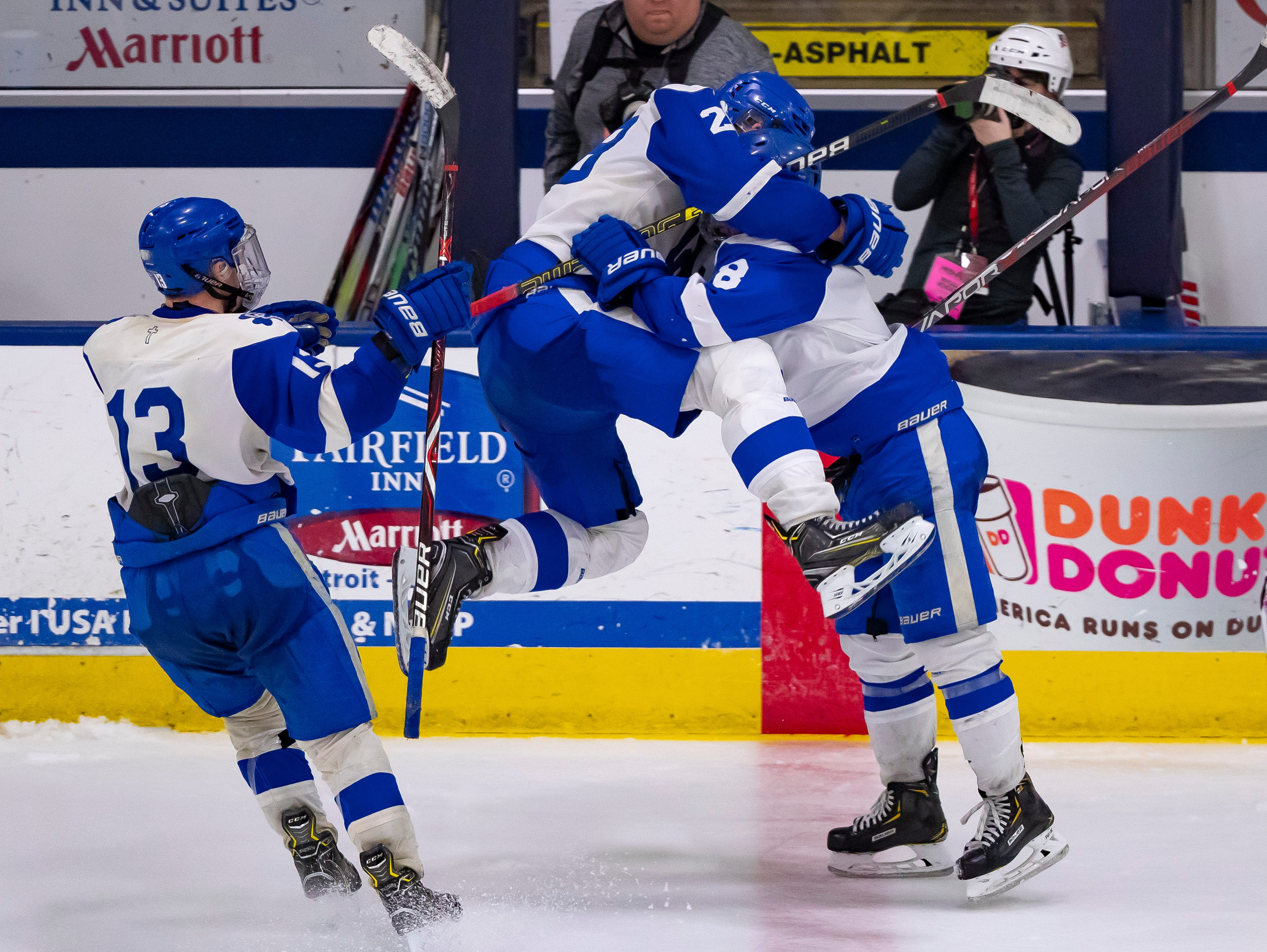 Ryan Marra (28) of Catholic Central celebrates his third-period, empty-net goal with teammate Joe Borthwick (8) and Zach Borchardt (13) during the MHSAA Division 1 Finals against Saginaw Heritage at USA Arena on March 9, 2019 in Plymouth, Michigan. Catholic Central won, 3-1.