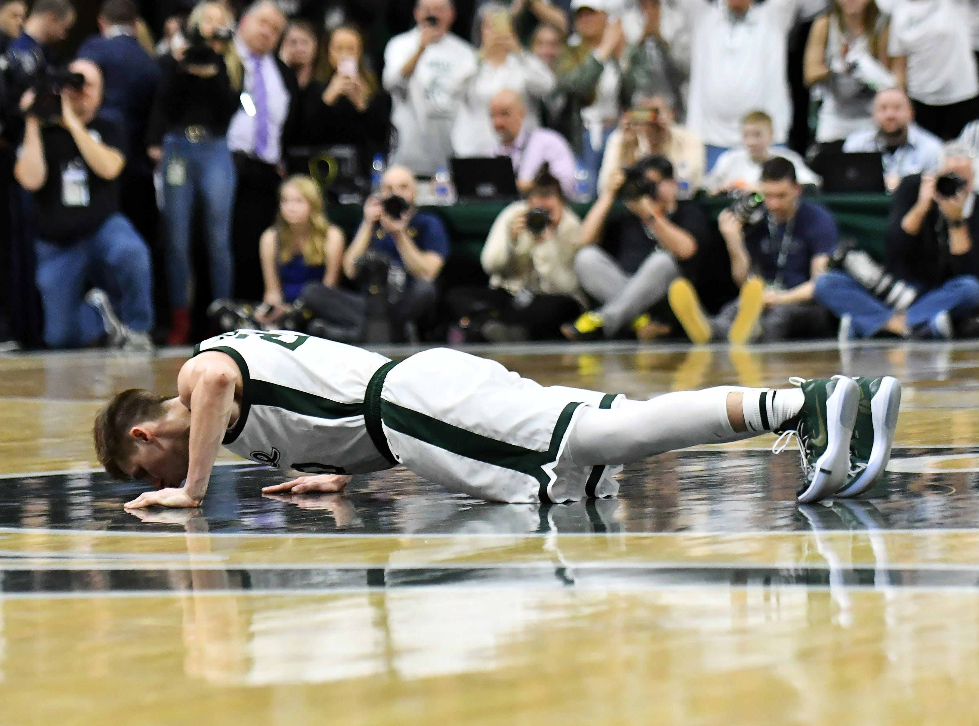 Michigan State senior guard Matt McQuaid (20) kisses the court before he exits the game in the second half.
