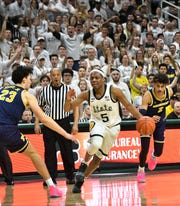 While the fans cheer, Michigan State guard Cassius Winston (5) weaves his way between Michigan defenders Michigan forward Brandon Johns Jr. (23) and Michigan guard Jordan Poole (2) in the second half.