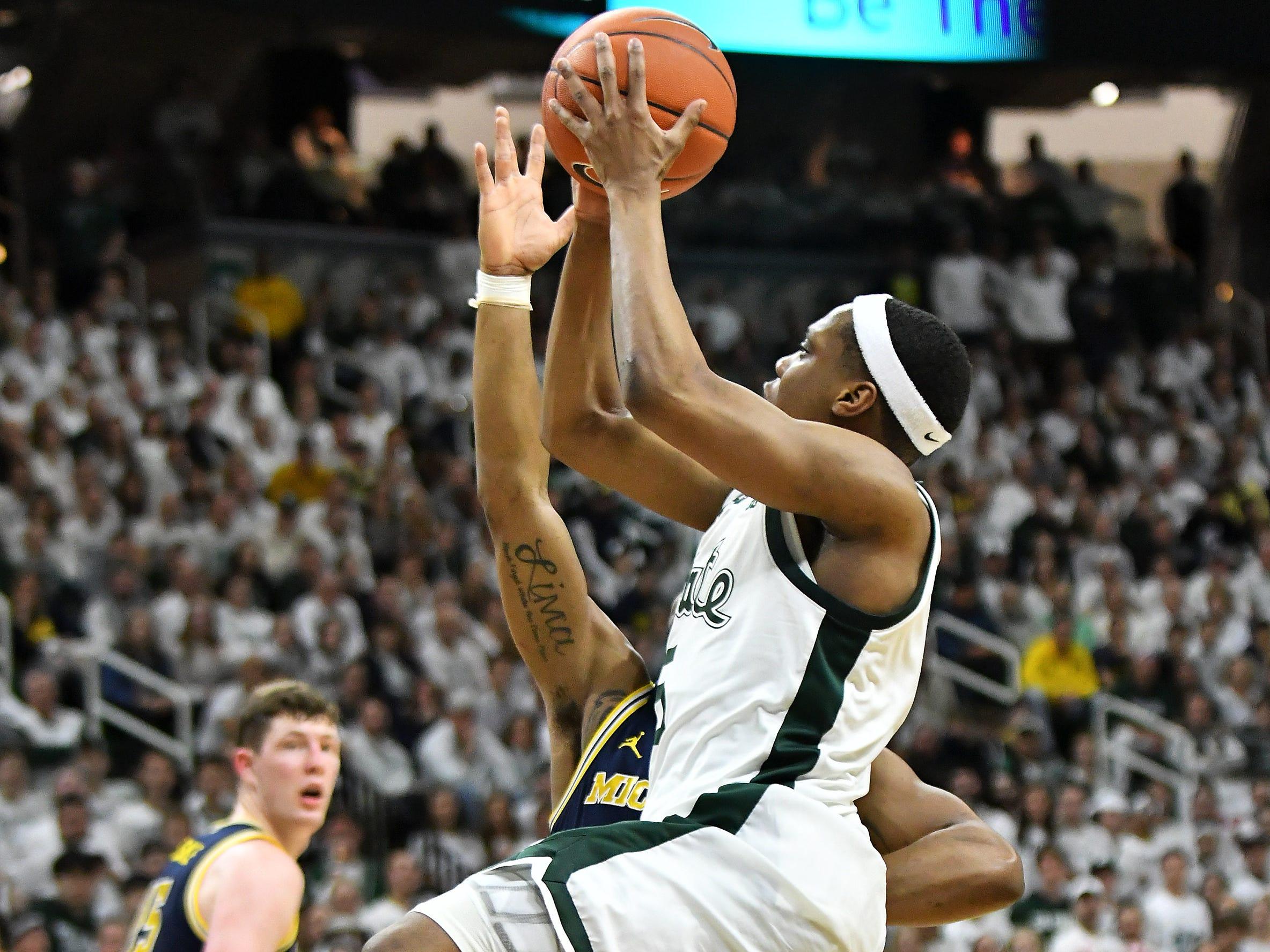 Michigan State guard Cassius Winston (5) drives on Michigan guard Zavier Simpson (3) in the second half.
