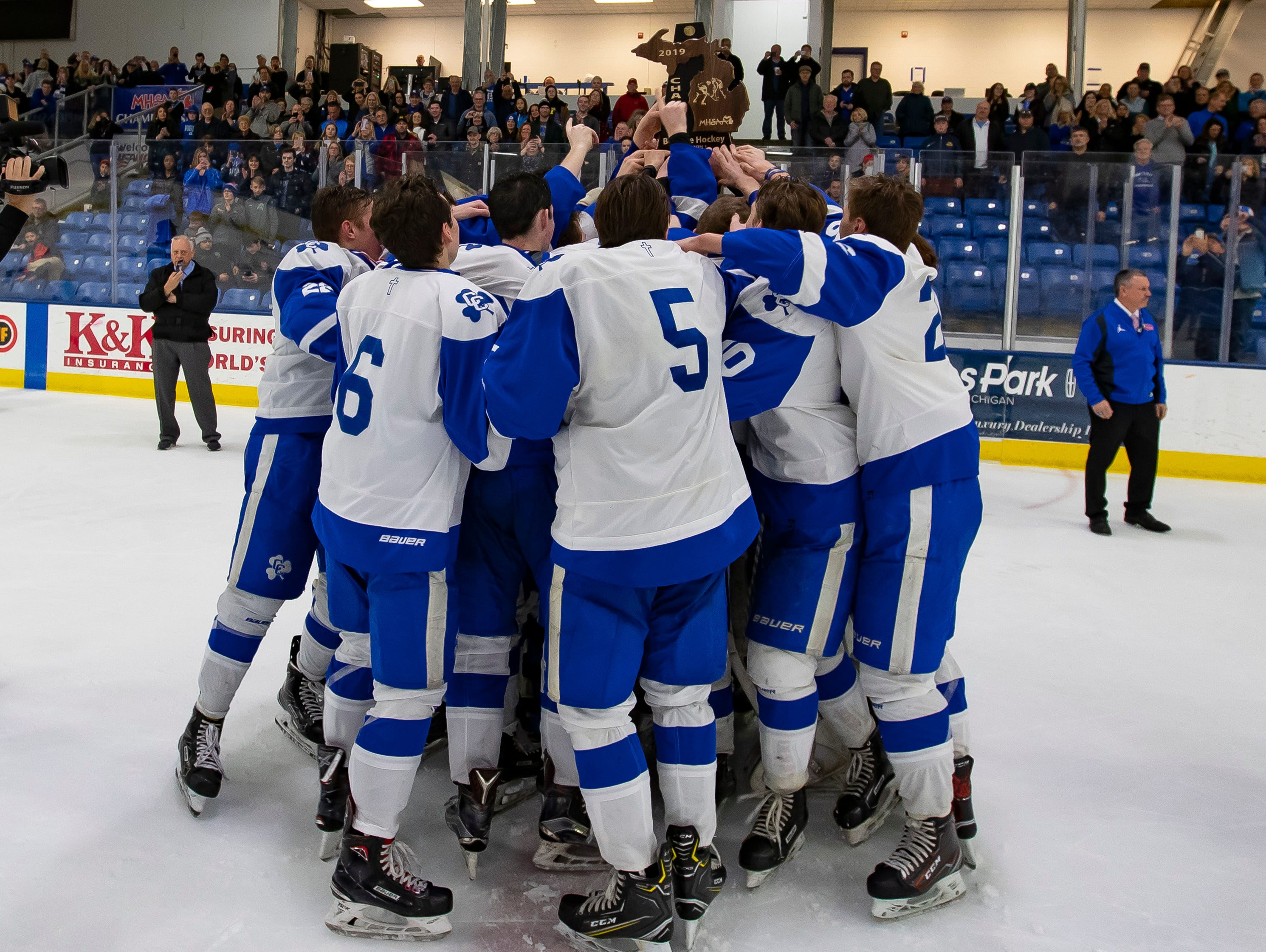 Catholic Central players receive their trophy after defeating Saginaw Heritage 3-1 to win the MHSAA Division 1 Championship.