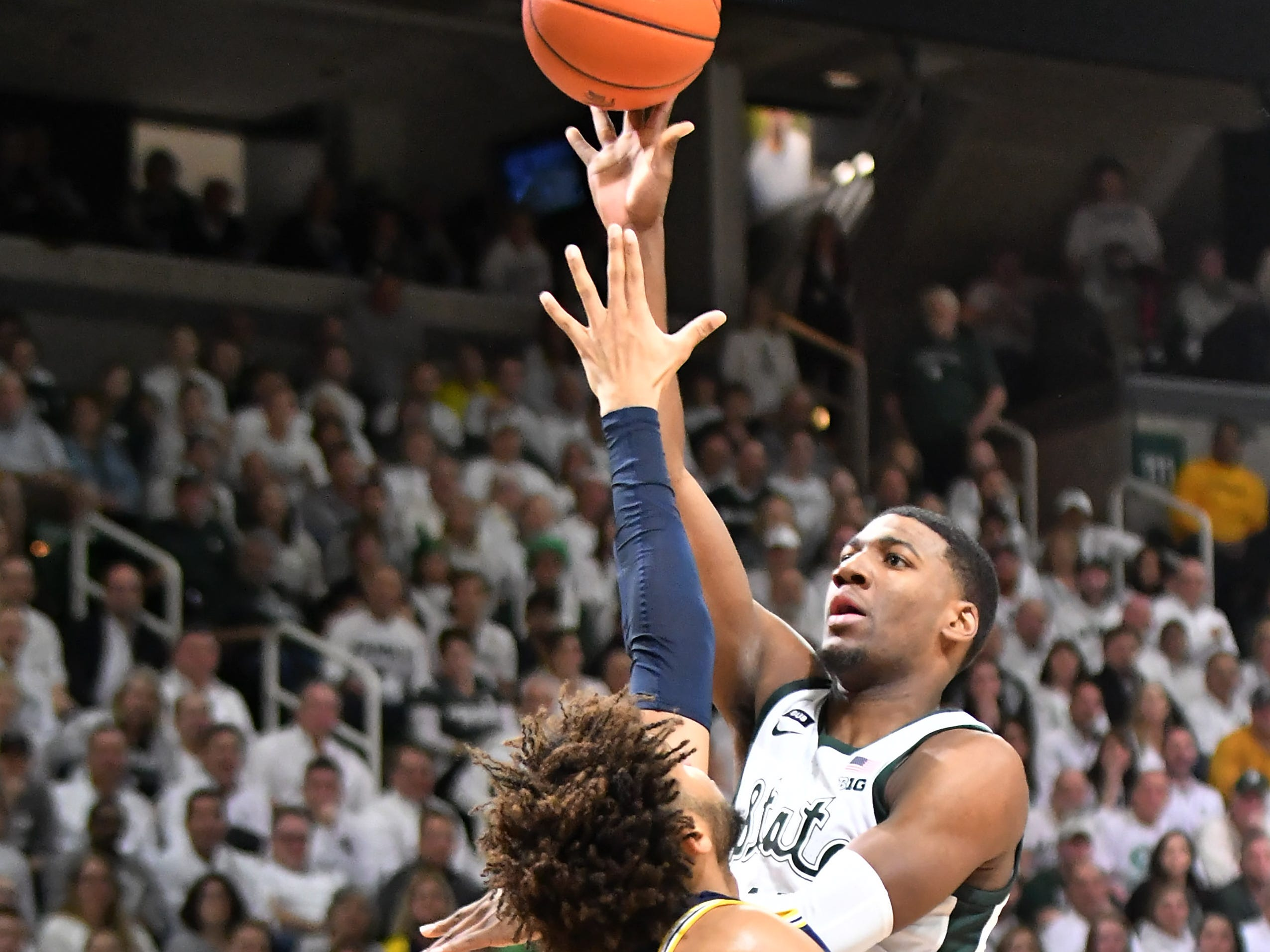 Michigan State forward Aaron Henry (11) shoots over Michigan forward Isaiah Livers (4) in the second half.