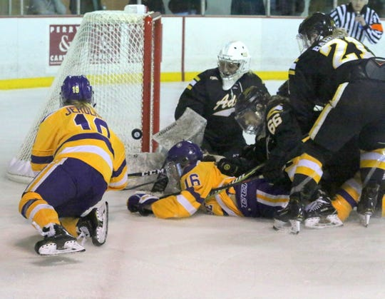 Maddy Jerolman of Elmira, left, eyes the puck as a scramble forms around Adrian goaltender Danisa Jandova during an NCAA Division III women's hockey quarterfinal March 9, 2019 at the Murray Athletic Center in Pine Valley