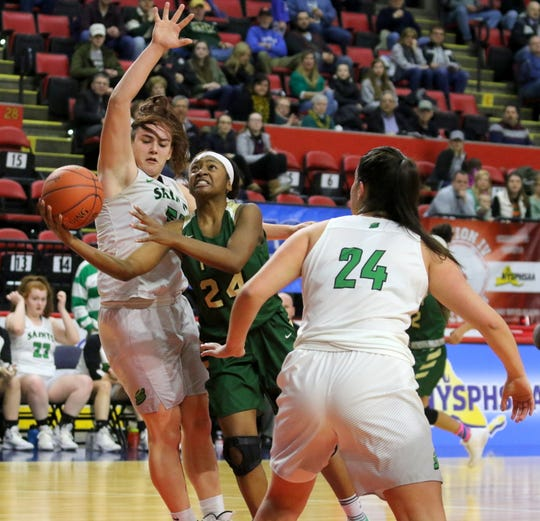 Julia Hauer of Seton Catholic Central gets set to block a shot from Roosevelt's Jaelen Daubon as Seton's Marina Maerkl looks on during a girls Class A regional game Sunday at the Floyd L. Maines Veterans Memorial Arena in Binghamton.
