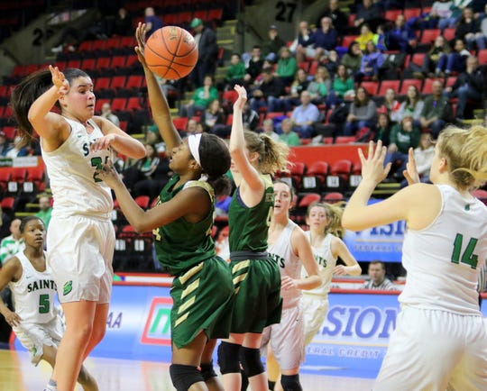 Marina Maerkl of Seton Catholic Central passes inside to Lily Combs as Roosevelt's Jaelen Daubon, left, and Kaitlyn McCabe defend during a girls Class A regional game Sunday at the Floyd L. Maines Veterans Memorial Arena in Binghamton.