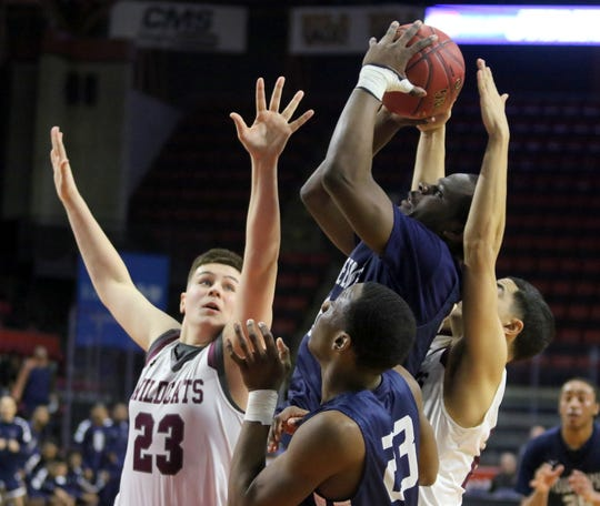 Tremell Reaves of Poughkeepsie goes up for a shot as Johnson City's Sean Moran (23) and Jaden Johns defend during a Class A boys basketball regional March 10, 2019 at the Floyd L. Maines Veterans Memorial Arena in Binghamton.