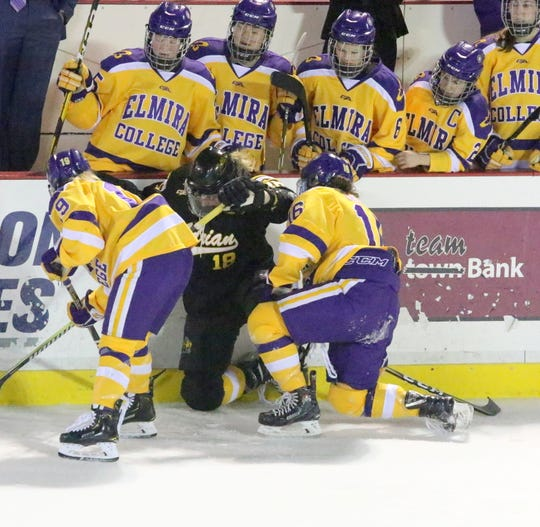 Elmira College's Maddy Jerolman (19) and Emma Crocker (16) battle for the puck with Adrian's Taylor Henthorne during an NCAA Division III women's hockey quarterfinal March 9, 2019 at the Murray Athletic Center in Pine Valley.