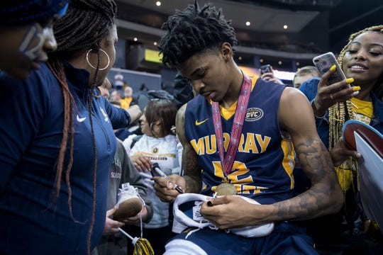 Murray State's Ja Morant signs a shoe he wore during a victory over Belmont in the Ohio Valley Conference championship game.