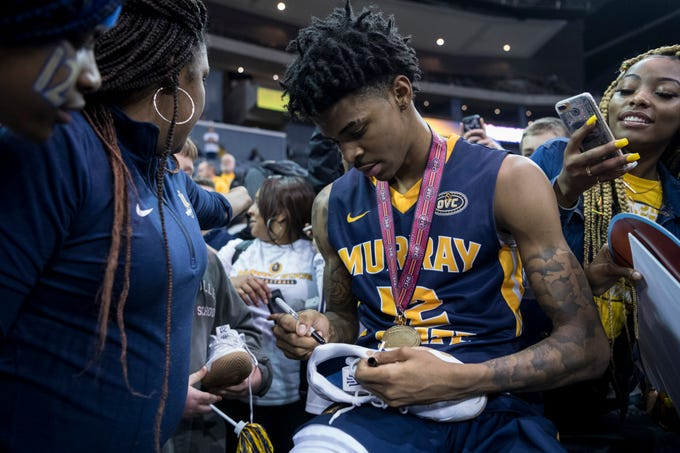Murray State's Ja Morant (12) autographs the Nike shoes he wore to give to a fan after winning the Ohio Valley Conference championship title over the Belmont University Bruins at Ford Center in Evansville, Ind., Saturday, March 9, 2019. The Racers defeated the Bruins, 77-65.