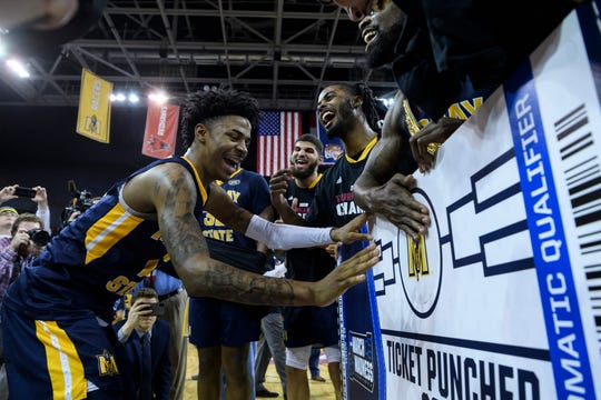 Murray State's Ja Morant (12) puts a Racers logo sticker on the NCAA Tournament ticket board following his team's Ohio Valley Conference championship victory at Ford Center in Evansville, Ind., Saturday, March 9, 2019. The Racers earned the OVC men's championship title after defeating the Bruins, 77-65.