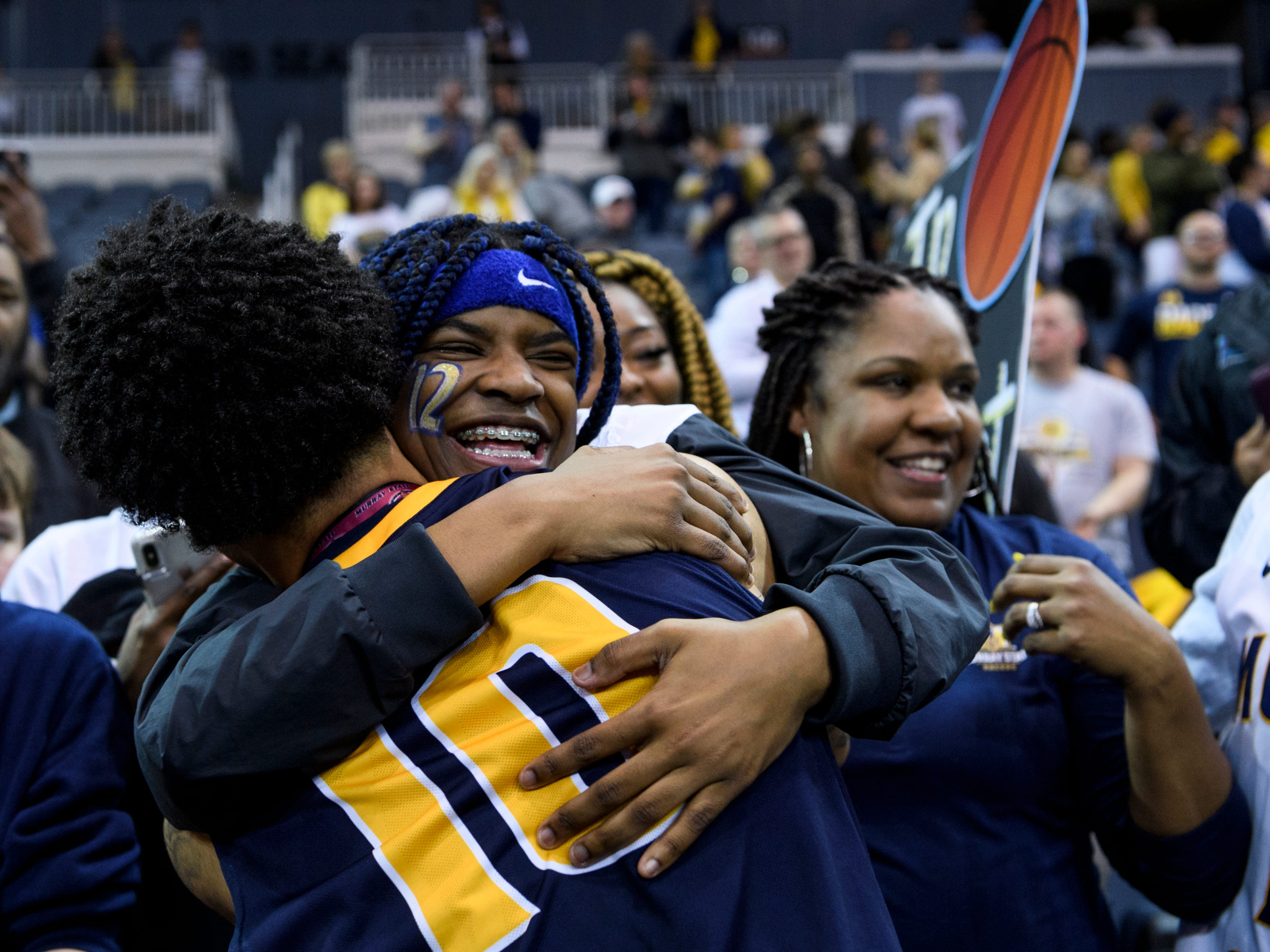 Murray State's Tevin Brown (10) receives a hug from Teniya Morant, Ja Morant's sister, following their Ohio Valley Conference championship win at Ford Center in Evansville, Ind., Saturday, March 9, 2019. The Racers earned the OVC men's championship title after defeating the Bruins, 77-65.