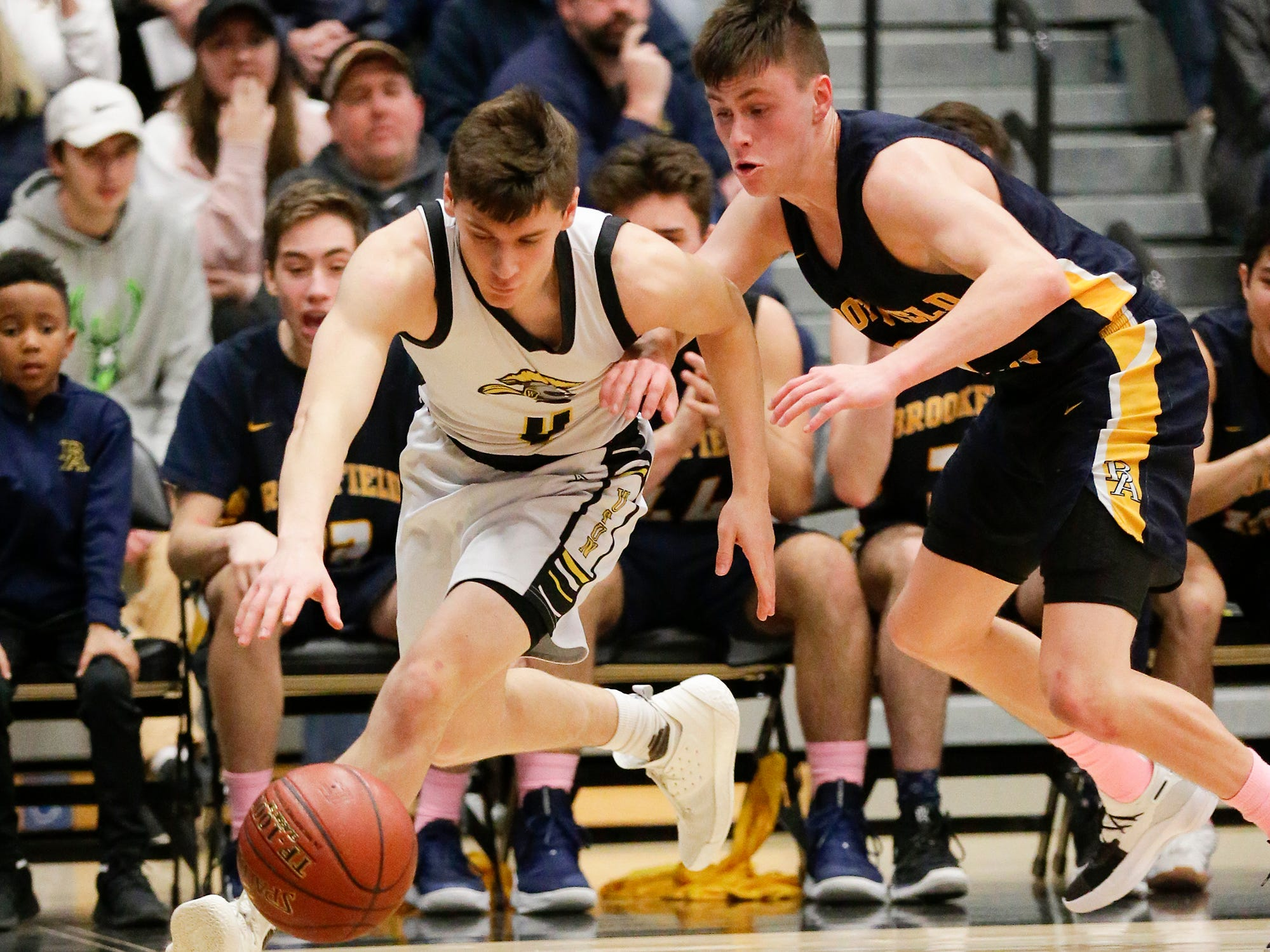 Waupun High School boys basketball's Benet Veleke (4) battles for a loose ball with Brookfield Academy's Aiden Clarey (1) during their WIAA division 3 sectional final game Saturday, March 9, 2019 in Brown Deer, Wis. Waupun won the game 64-58 and will advance to the state tournament.