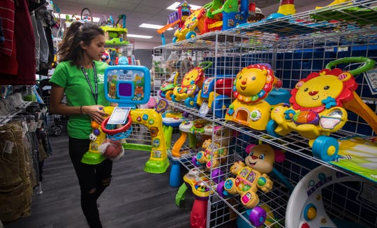 Kimberly Guzman stocks the shelves with newly arrived merchandise at Once Upon a Child in Cape Coral.