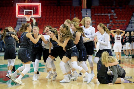 Bay Port players mob Bay Port's Emma Nagel (23) after winning the Division 1 championship match over Middleton at the WIAA state girls basketball tournament at the Resch Center on Saturday, March 9, 2019, in Ashwaubenon, Wis.