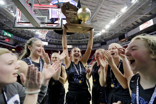 Bay Port's Emma Nagel (23) carries the championship trophy toward the student section after the WIAA Division 1 state championship game March 9 at the Resch Center in Ashwaubenon.