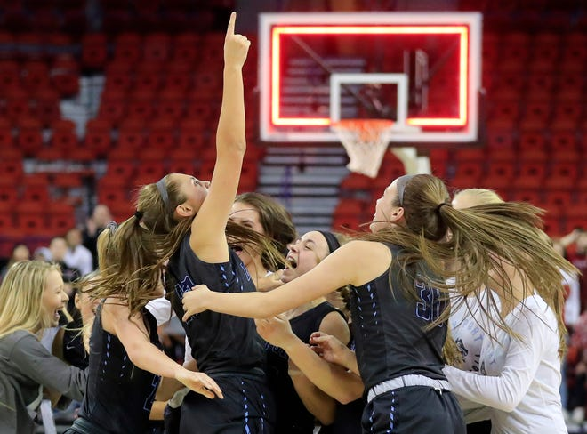 Bay Port players mob teammate Emma Nagel (23) after winning the Division 1 state championship over Middleton on Saturday at the Resch Center in Ashwaubenon.