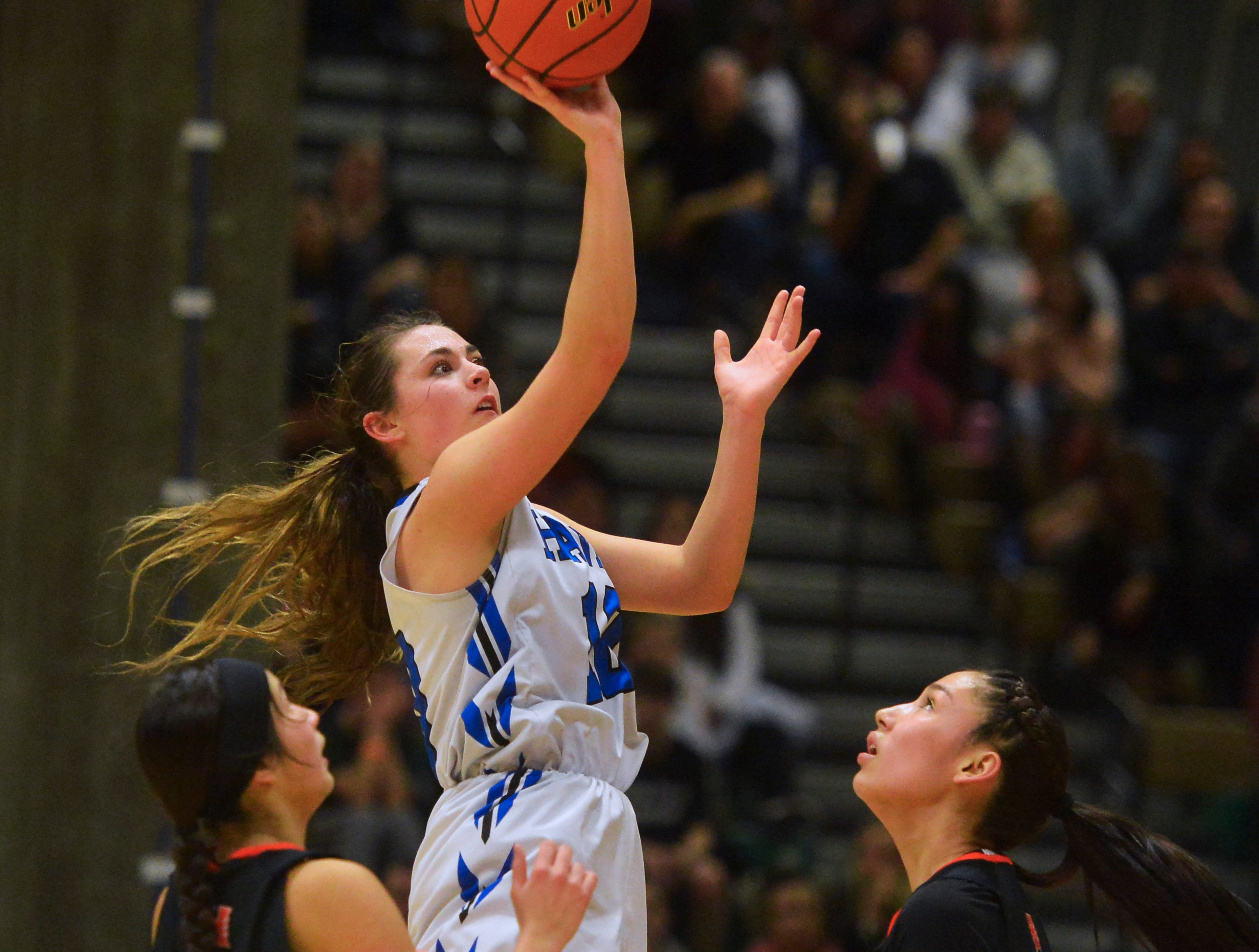 Havre's Kyndall Keller takes a jump shot between Hardin's Ivery Fritzler and Sossity Spotted Wolf during the title game of the State Class A Basketball Tournament in the Four Seasons Arena, Saturday.