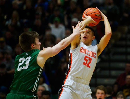 Hardin 's Famous Lefthand attempts a shot over Billings Central's Tyler Gray in the championship game of the State Class A Basketball Tournament in the Four Seasons Arena, Saturday.