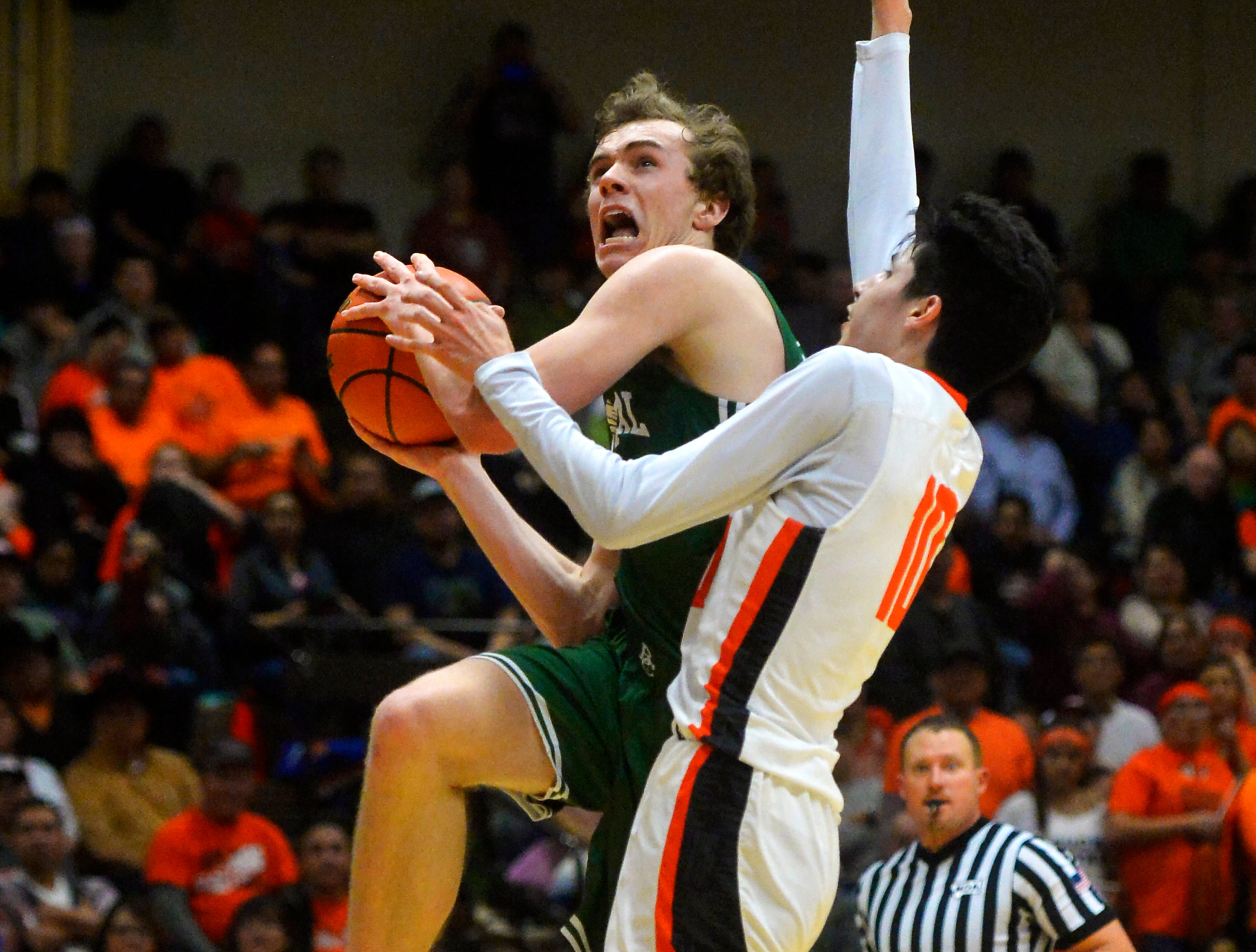 Billings Central's Joe Byorth draws contact from Hardin's Trae Hugs on a shot attempt in the title game of the State Class A Basketball Tournament in the Four Seasons Arena, Saturday.