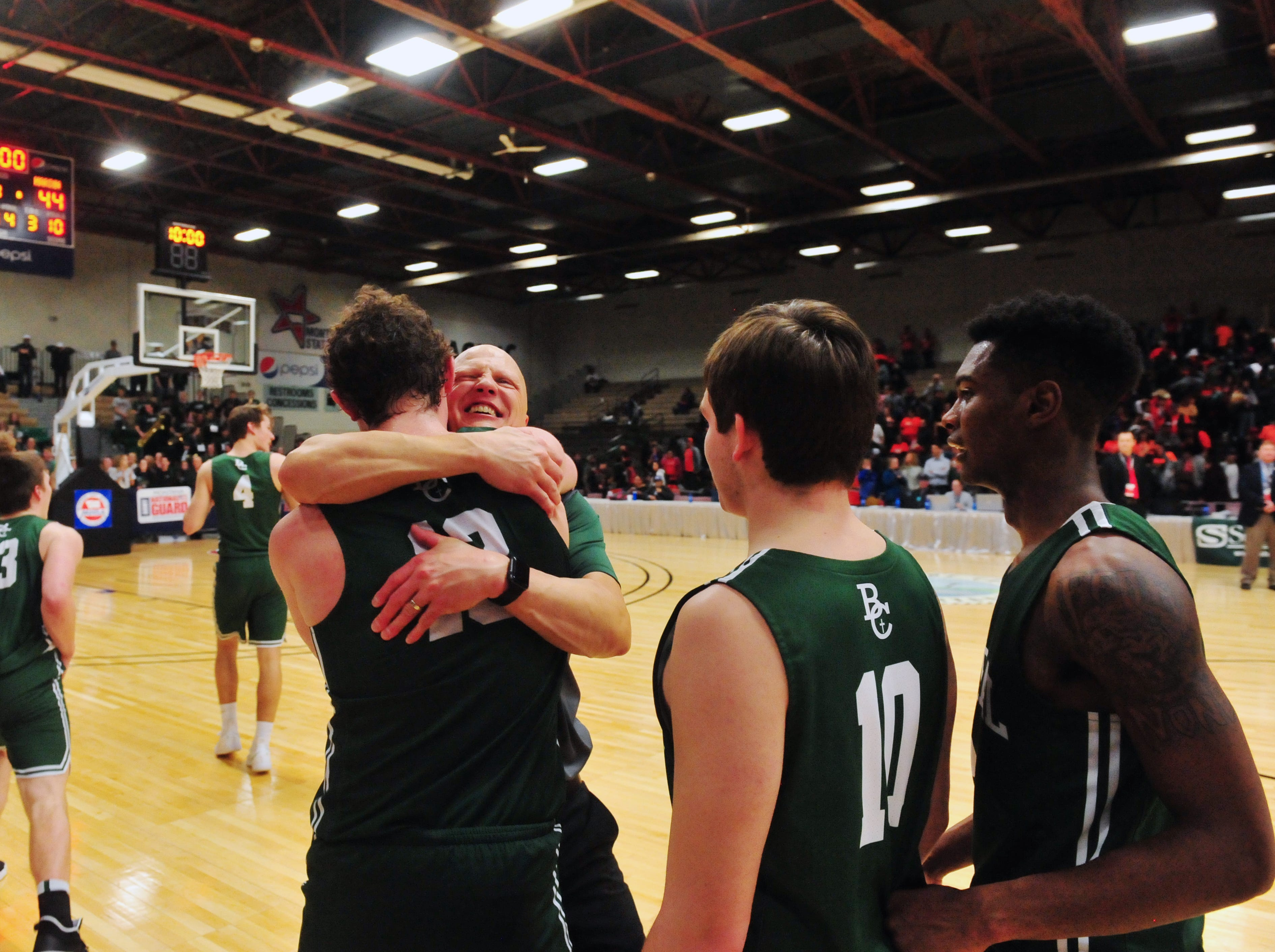 Billings Central coach Jim Stergar congratulates his team on their 62-44 victory over Hardin in the championship game of the State Class A Basketball Tournament in the Four Seasons Arena, Saturday.