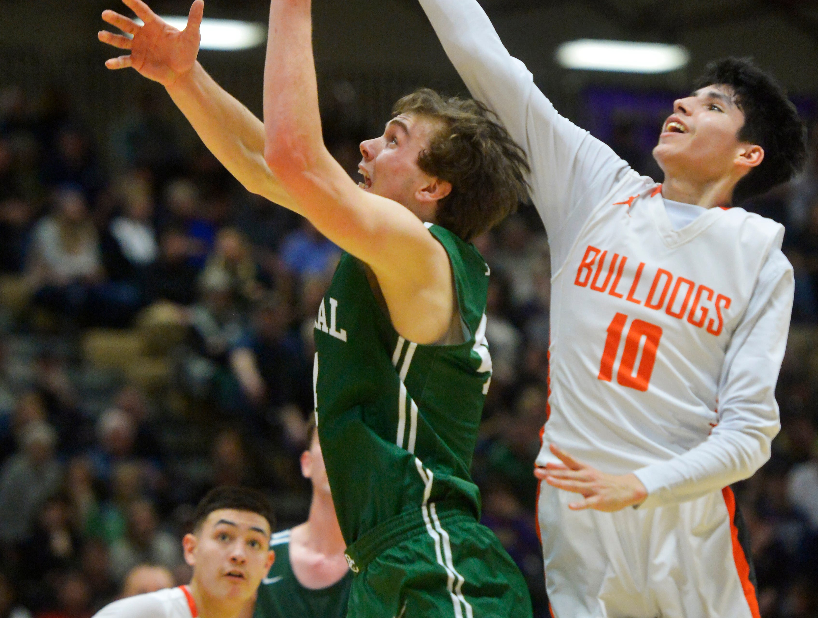 Billings Central's Joe Byorth attempts a layup as Hardin's Trae Hugs defends  in the title game of the State Class A Basketball Tournament in the Four Seasons Arena, Saturday.
