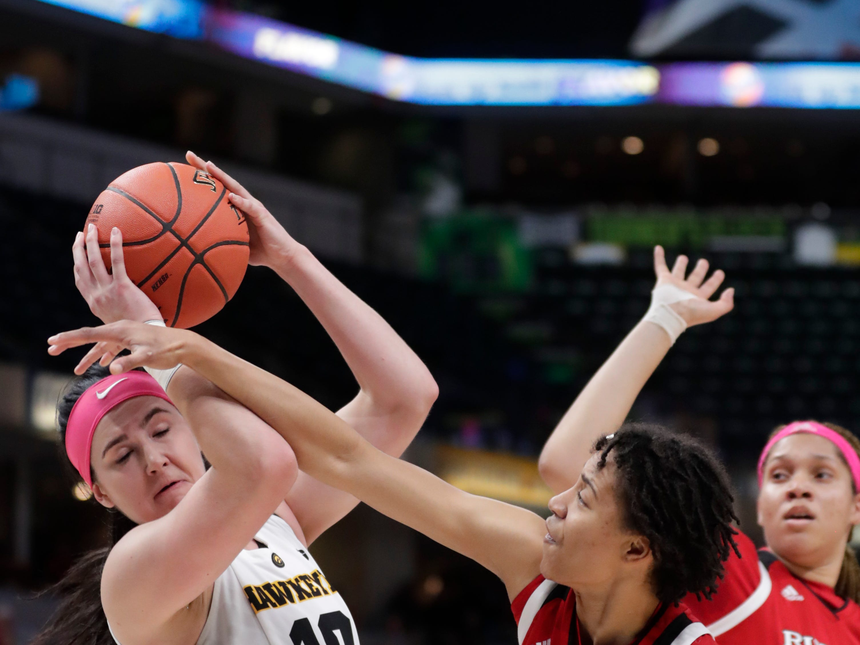 Rutgers guard Zipporah Broughton (1) fouls Iowa forward Megan Gustafson (10) in the first half of an NCAA college basketball semifinal game at the Big Ten Conference tournament in Indianapolis, Saturday, March 9, 2019.