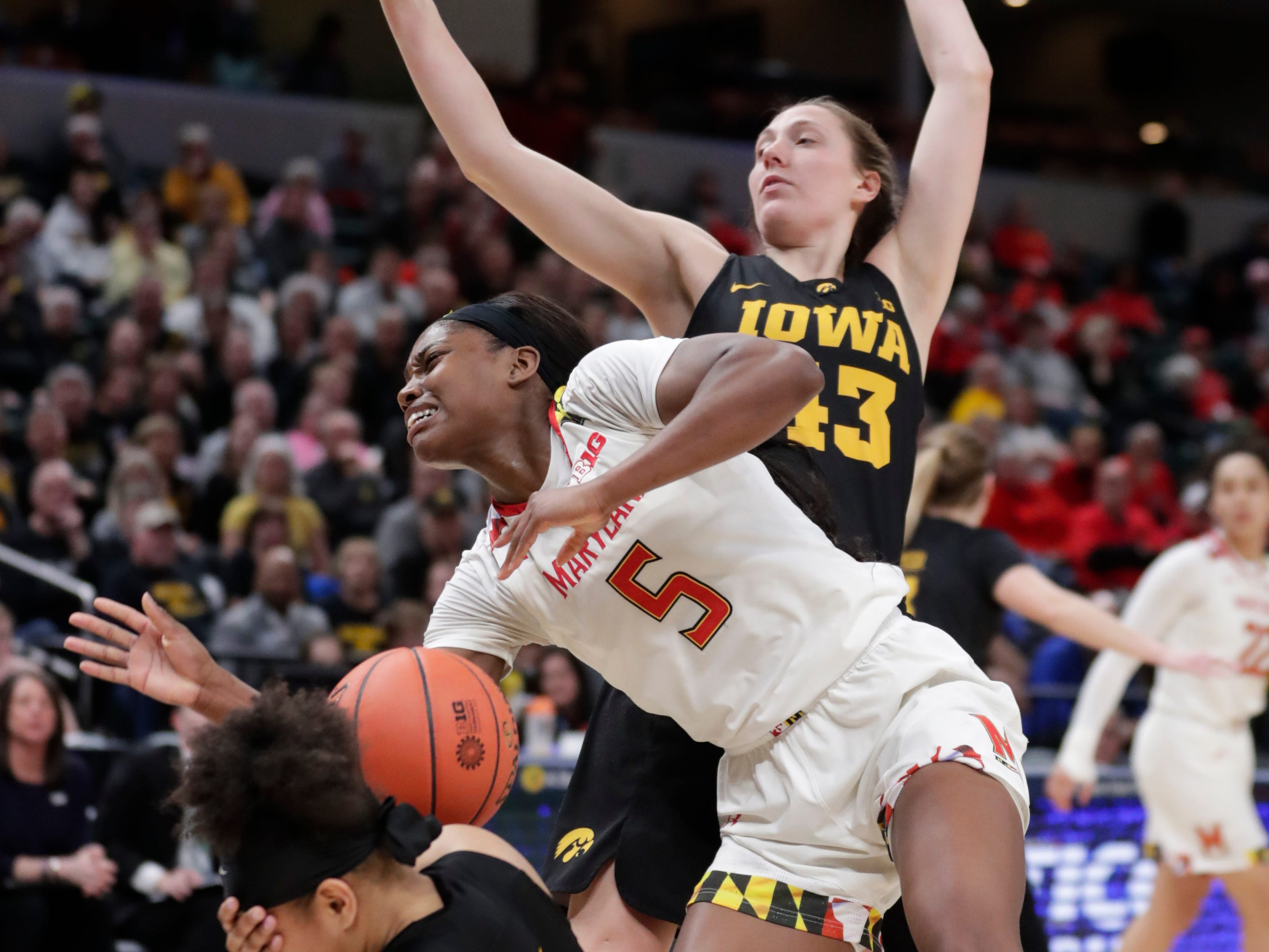 Iowa guard Tania Davis (11) takes hard contact in a battle with Maryland guard Kaila Charles (5) and Iowa's Amanda Ollinger (43) during the Big Ten women's championship game.