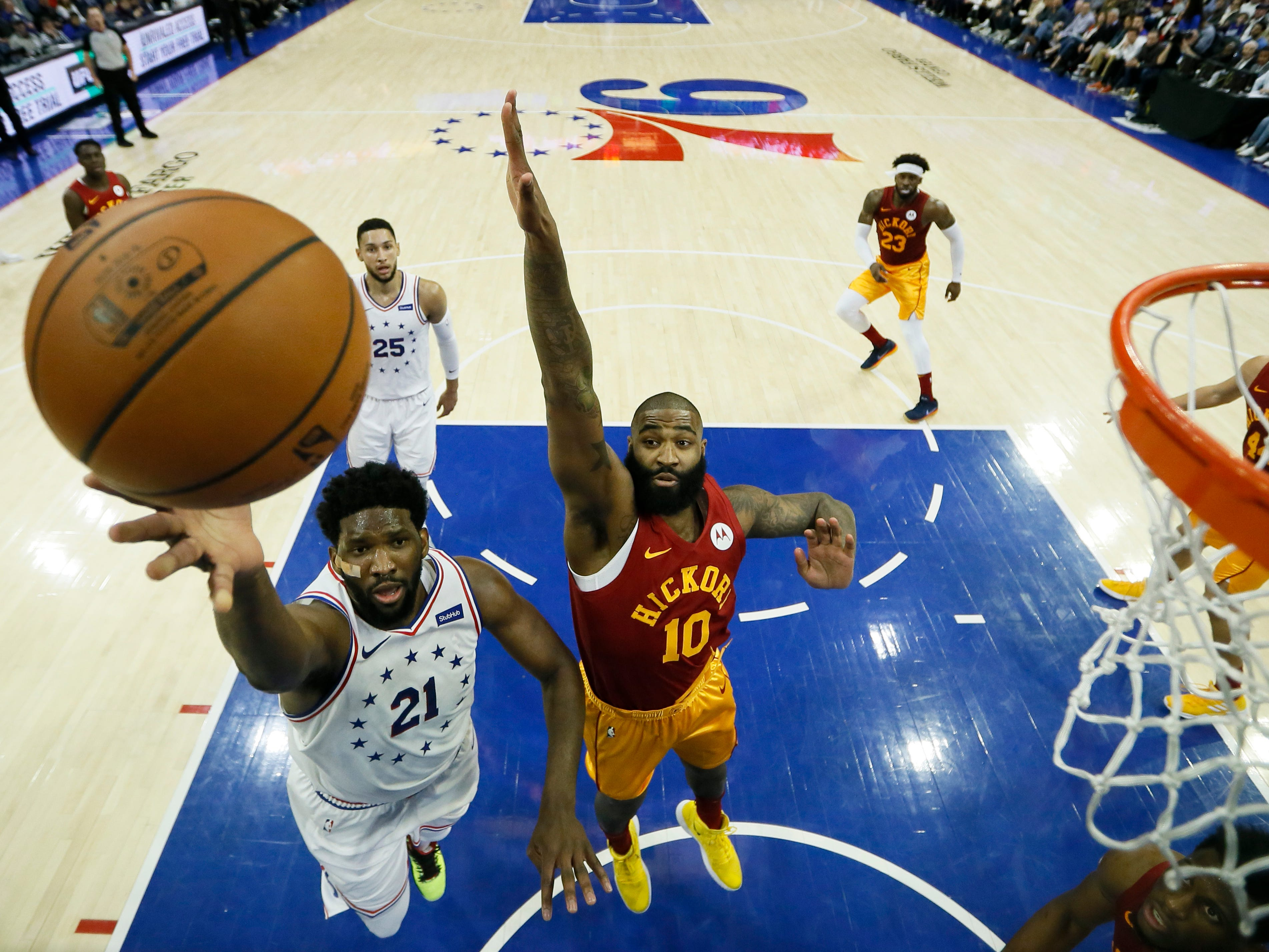 Philadelphia 76ers' Joel Embiid (21) goes up for a shot past Indiana Pacers' Kyle O'Quinn (10) during the first half of an NBA basketball game, Sunday, March 10, 2019, in Philadelphia.