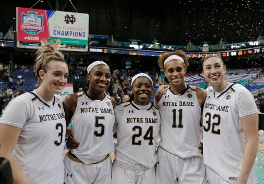 Notre Dame players Marina Mabrey (3), Jackie Young (5), Arike Ogunbowale (24), Brianna Turner (11) and Jessica Shepard (32) pose for a photo after their team defeated Louisville in an NCAA college basketball game in the championship of the Atlantic Coast Conference women's tournament in Greensboro, N.C., Sunday, March 10, 2019.