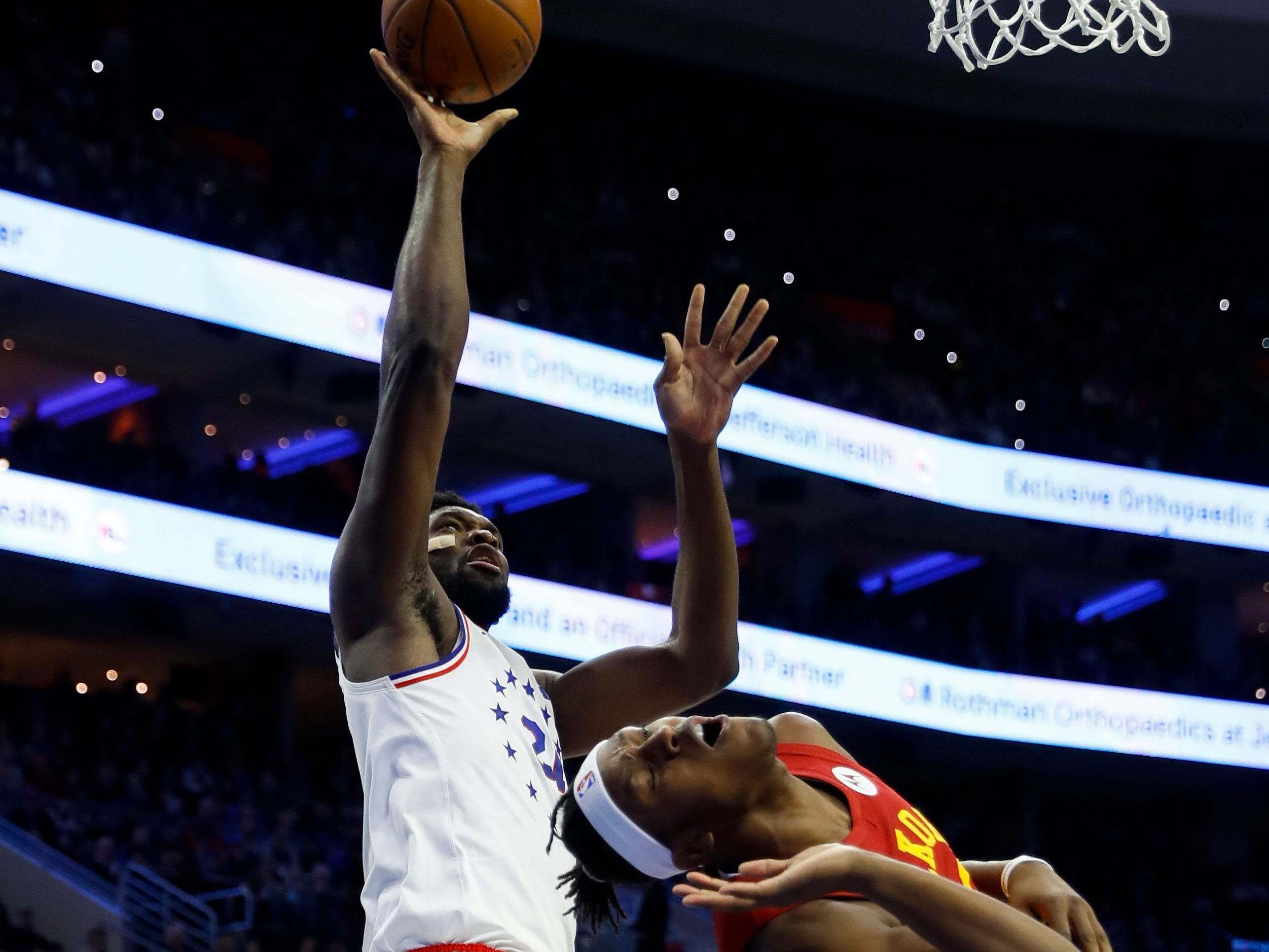 Philadelphia 76ers' Joel Embiid, left, goes up for a shot past Indiana Pacers' Myles Turner during the first half of an NBA basketball game, Sunday, March 10, 2019, in Philadelphia.