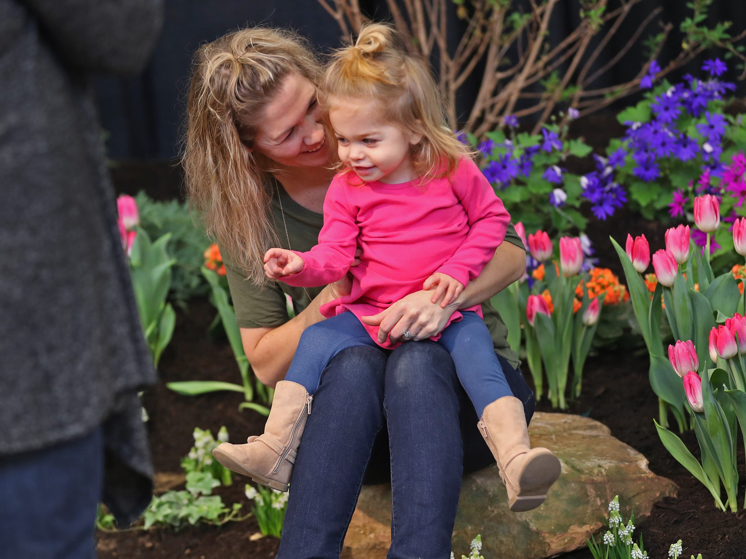 Rachel Drake poses for a photo with her daughter Delaney Drake, 2, against a colorful backdrop of the JDK Landscaping garden and patio, at the Indiana Flower + Patio Show, at the Indiana State Fairgrounds, Sunday, March 10, 2019.